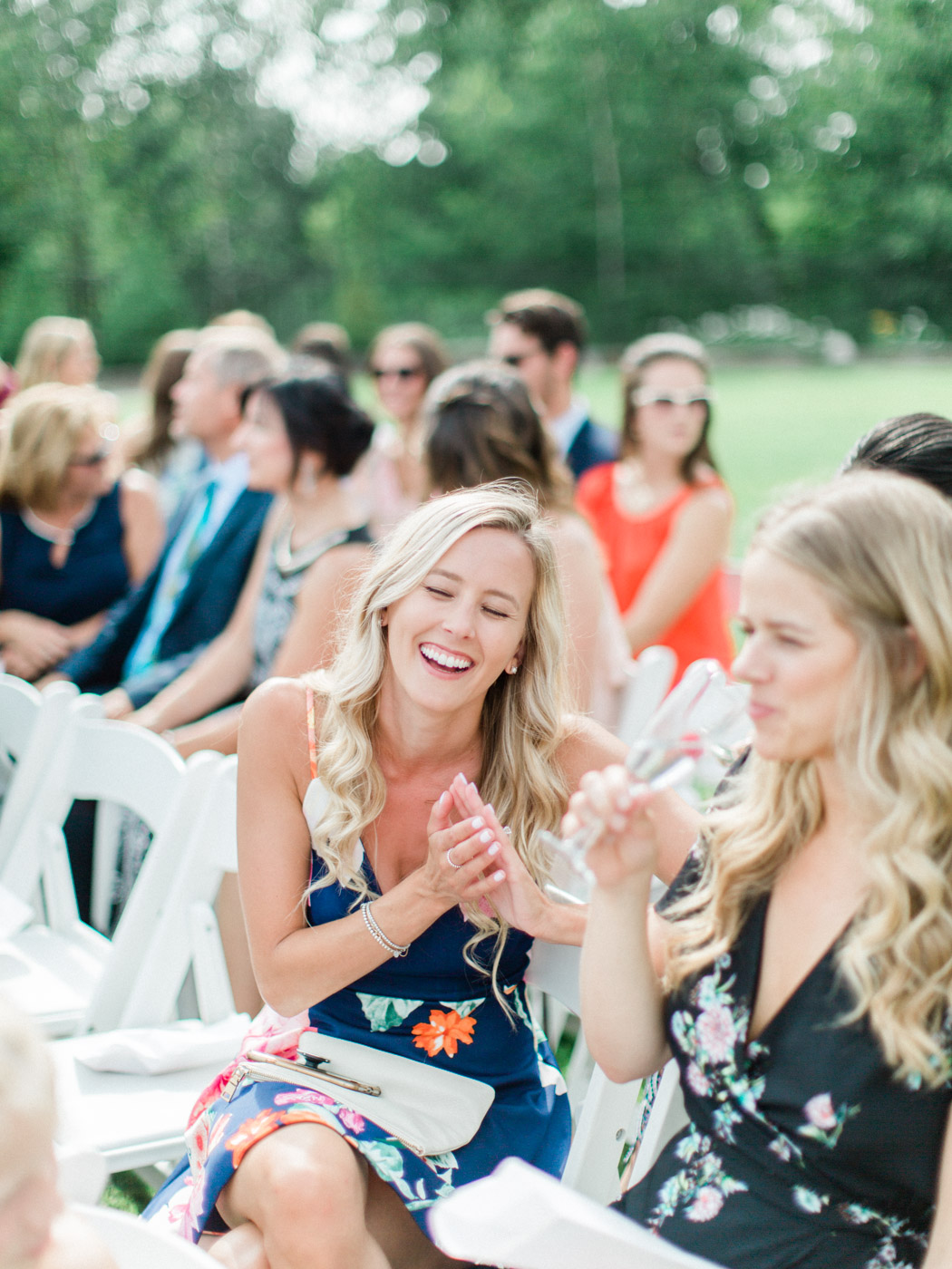 Documentary candid photograph from beautiful outdoor summer ceremony under floral arch in Muskoka.  Captured at the J.W. Marriott Rosseau by Muskoka wedding photographer Corynn Fowler Photography.