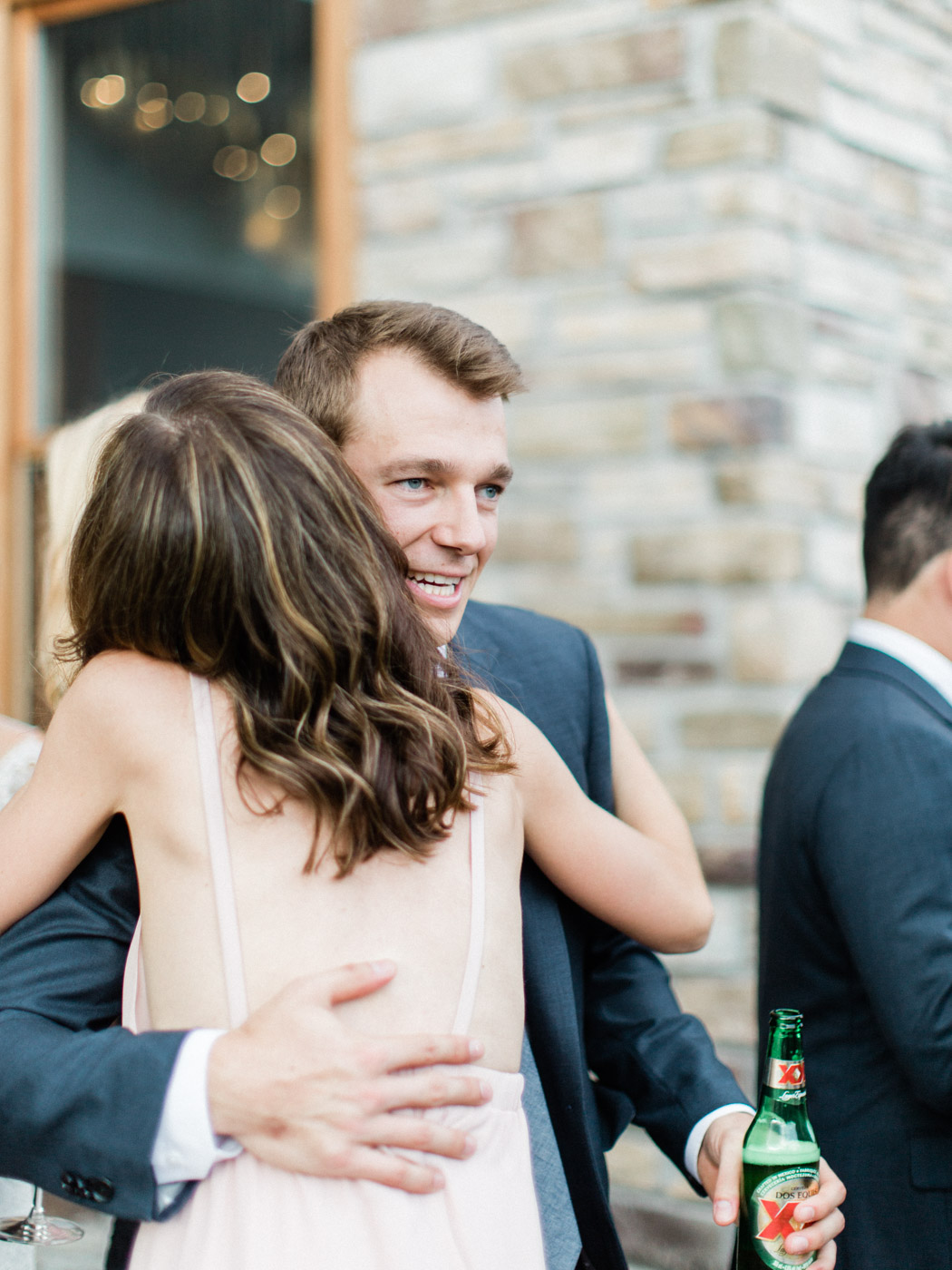 Candid documentary photograph of guests and couple at outdoor reception in Muskoka.  Captured by wedding photographer Corynn Fowler Photography.