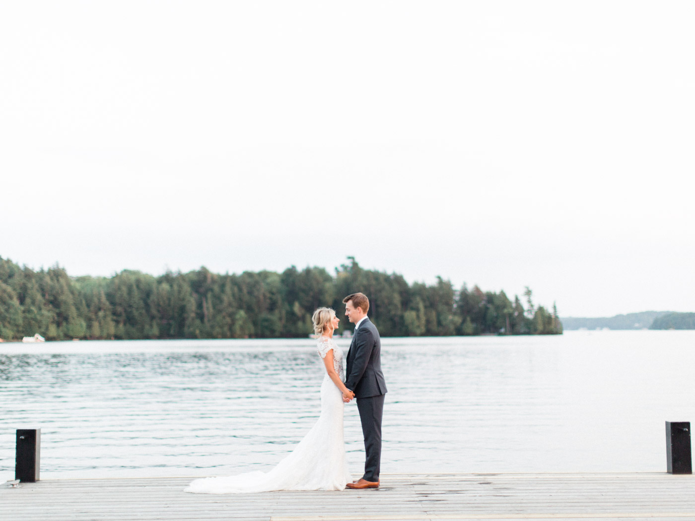Romantic fine art wedding photography portrait of the bride and groom by the beach at sunset.  Captured by Muskoka wedding photographer Corynn Fowler Photography.