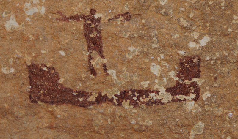 A detail from the rock art of the White Shaman cave shows what is believed to be a man and a small boat, possibly a canoe.    Photo by: Colin McDonald