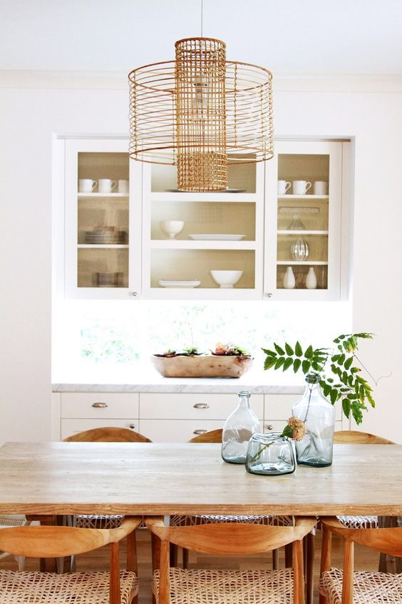 This photo illustrates my favorite option for incorporating a little hip rattan into your space - with a light fixture! There are so many cool and modern rattan lights on the market, and can I mention, the price points won't break your bank! This modern rattan light in this bohemian dining space is so simple and chic.