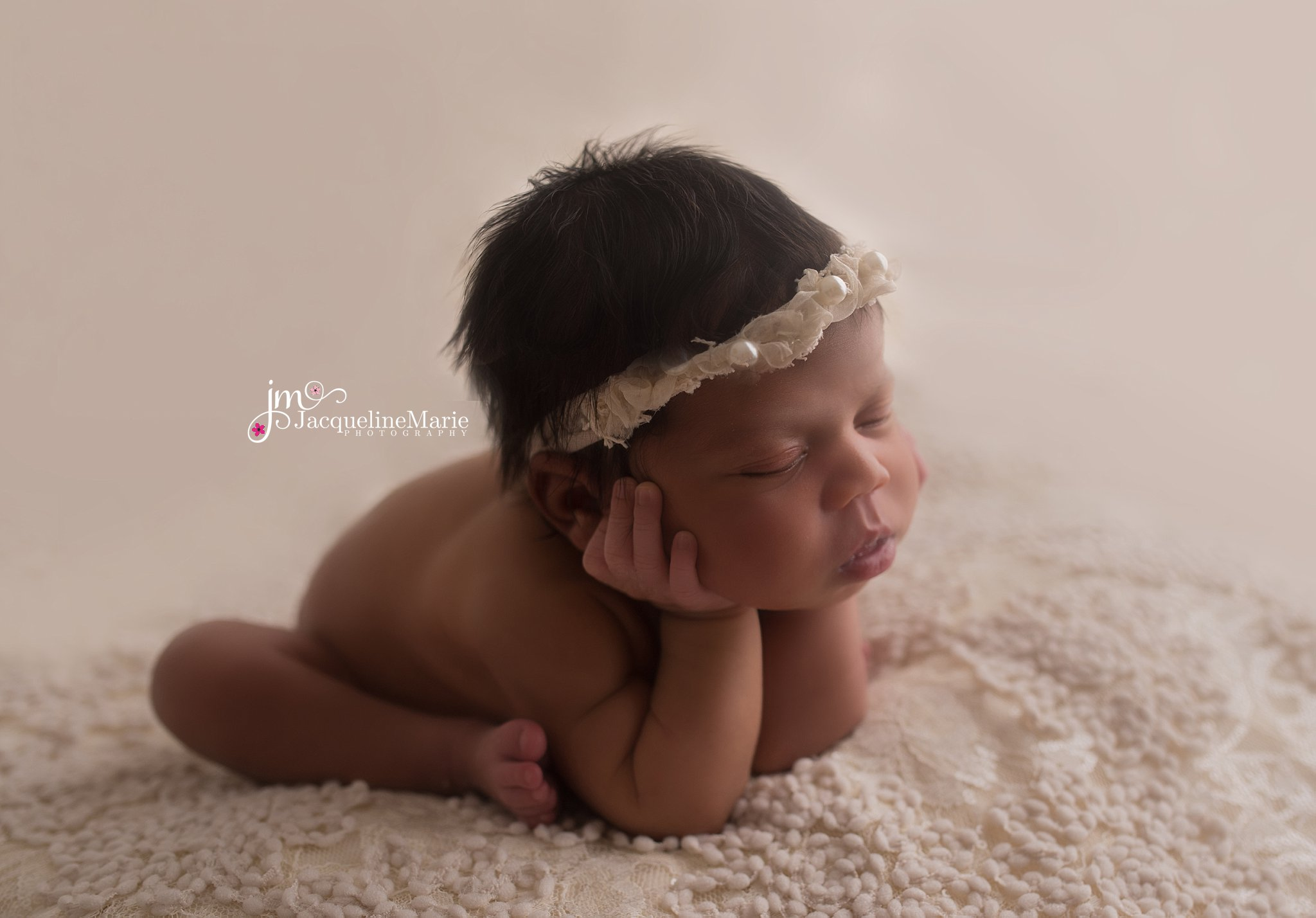 Columbus ohio newborn photographer features baby girl posed with head in hands while wearing cream pearl headband