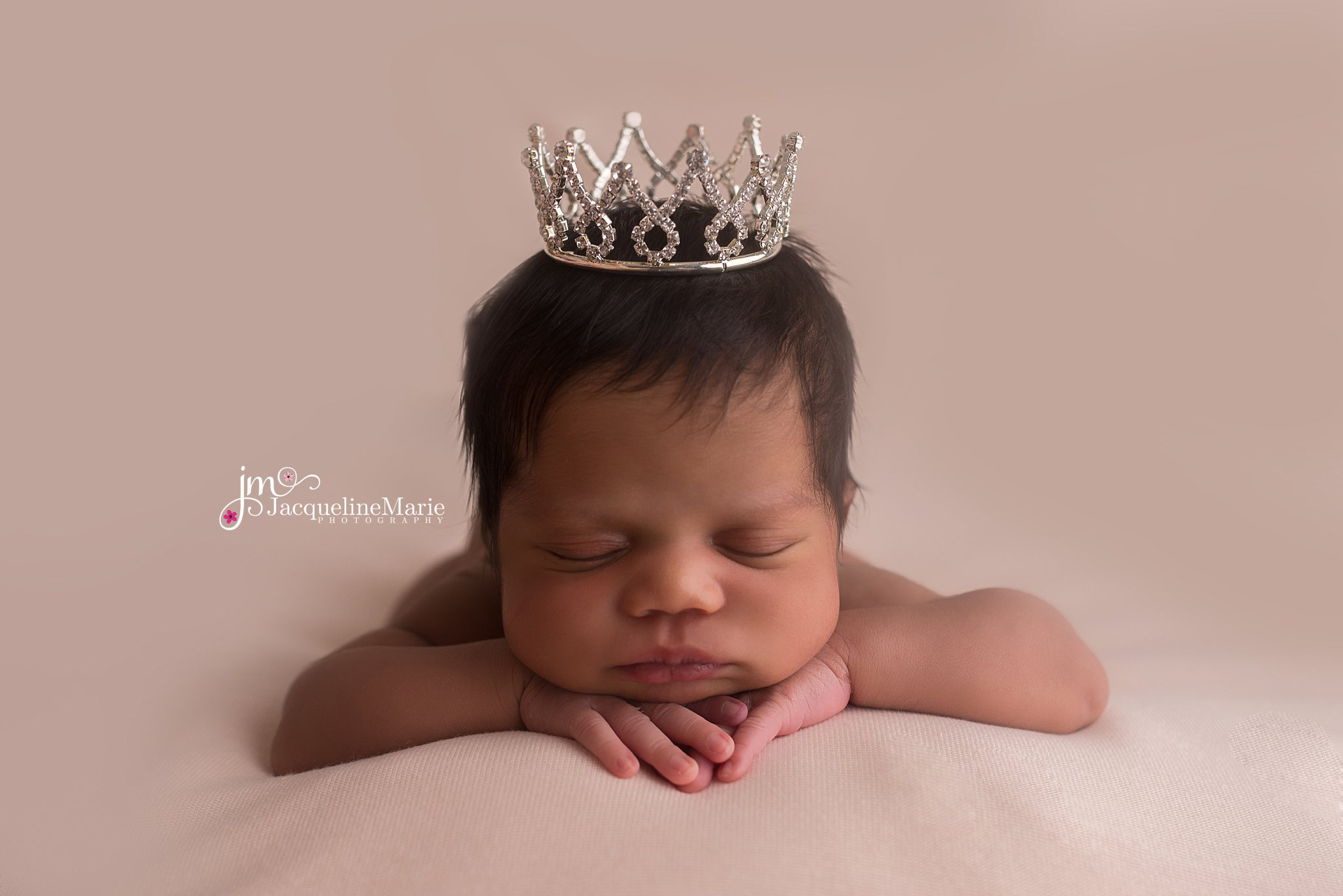 newborn baby girl with lots of hair wears rhinestone crown for newborn photography pictures in Columbus ohio