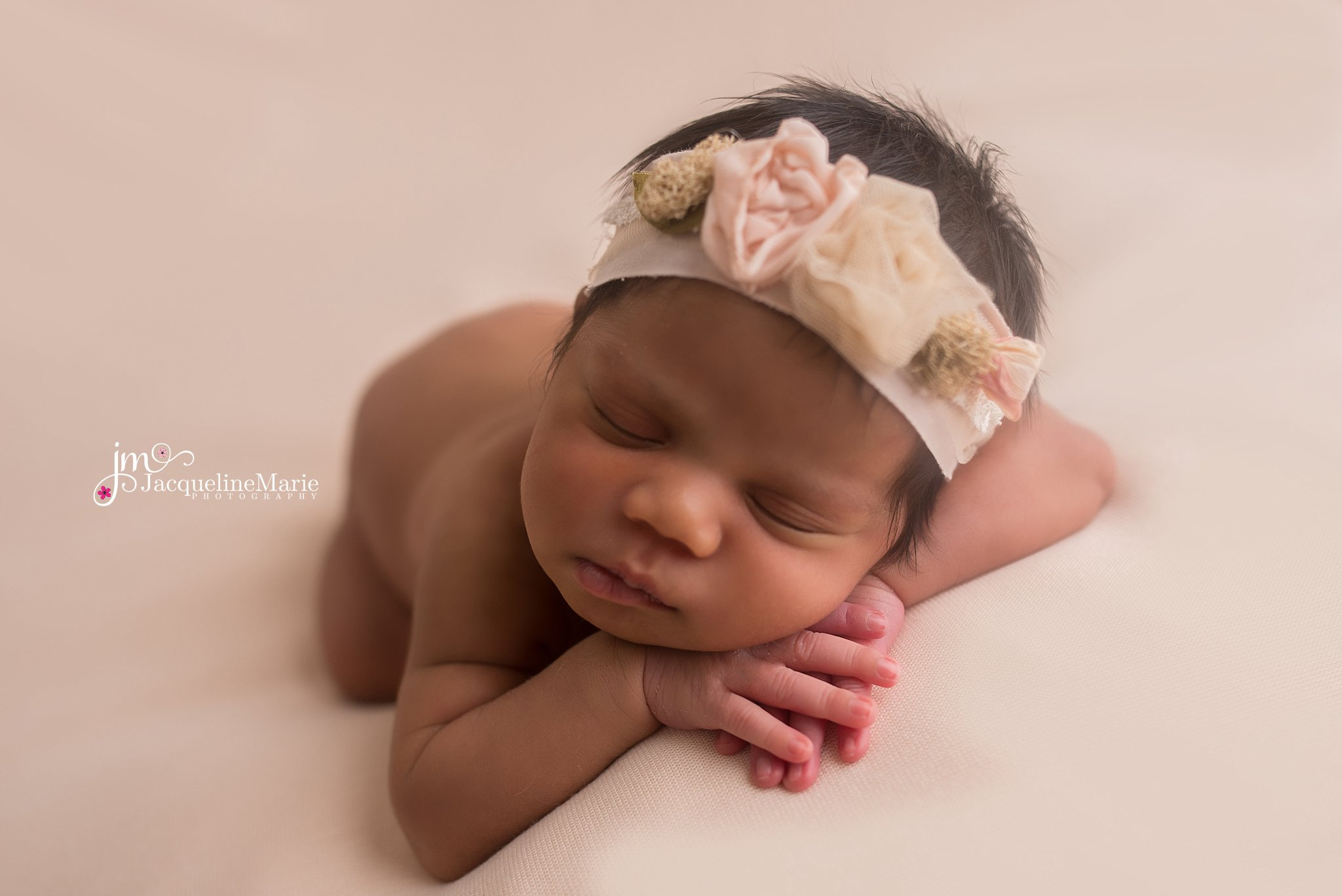 Columbus ohio newborn wears pink and cream floral headband with hands crossed for newborn photography session