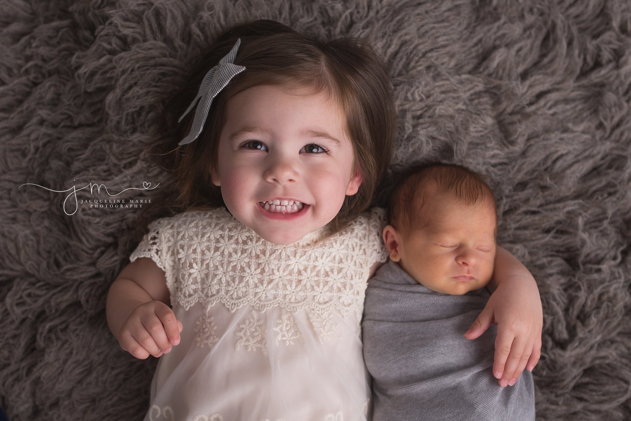 sibling pose featuring older sister holding baby brother for newborn pictures in Columbus Ohio