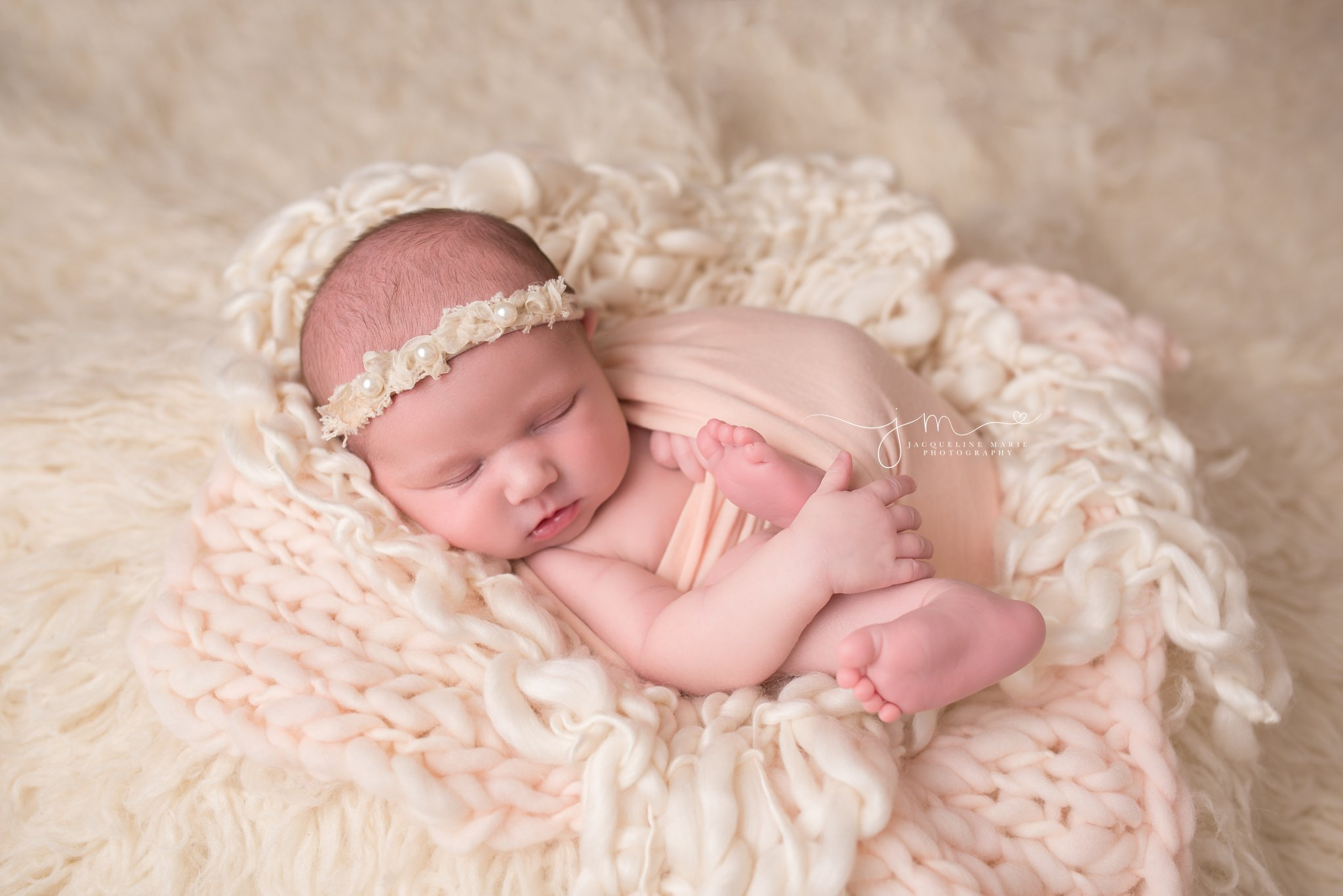 Columbus Ohio newborn baby featured in pink wrap and pearl headband at Jacqueline Marie Photography studio