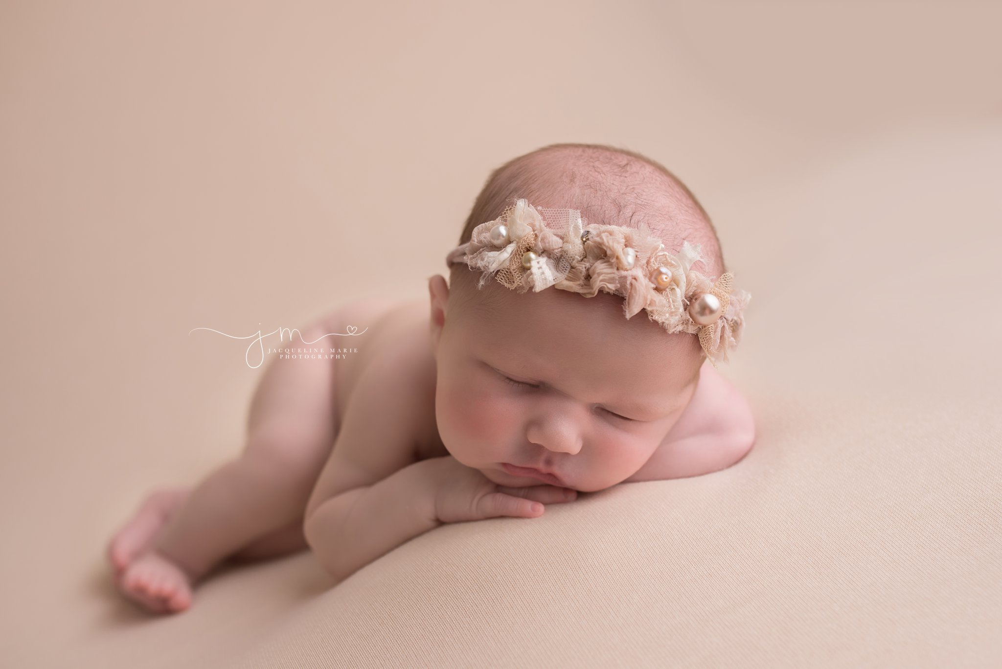 Columbus Ohio newborn wears pearl headband for portrait on blush pink blanket at Jacqueline Marie Photography
