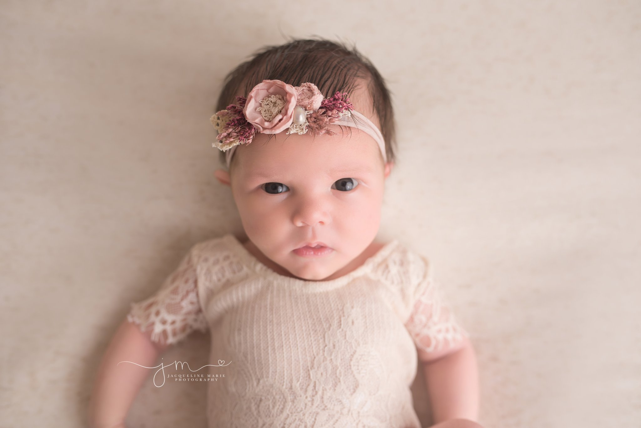 newborn baby girl in Columbus Ohio wears headband for awake newborn pictures