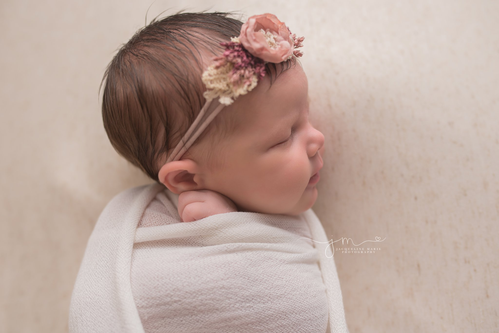 newborn baby is swaddled with hands peeking out in photography session at Columbus Ohio studio