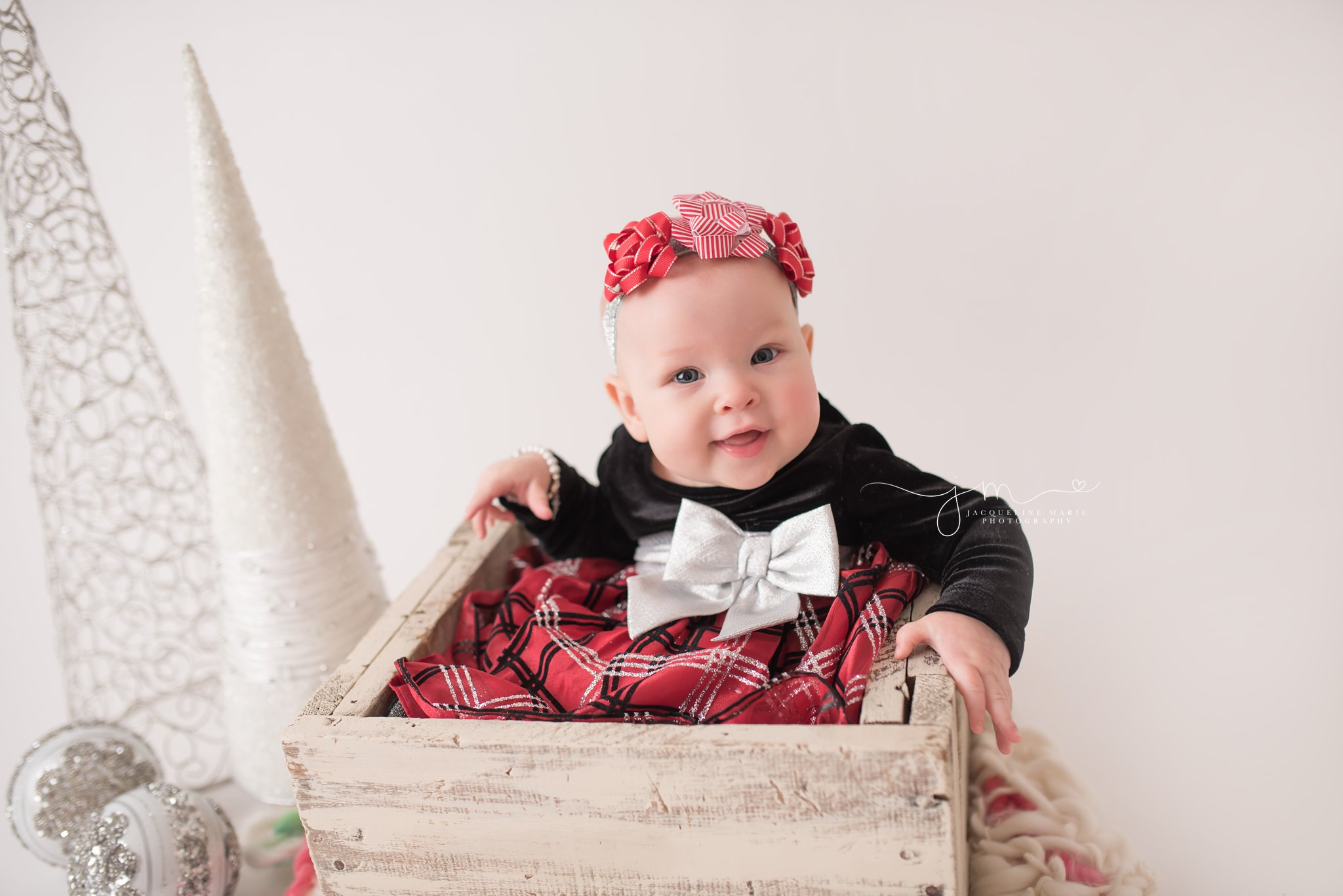 Columbus Ohio newborn and baby photographer features baby sitting in wooden crate for Christmas portrait at Jacqueline Marie Photography studio