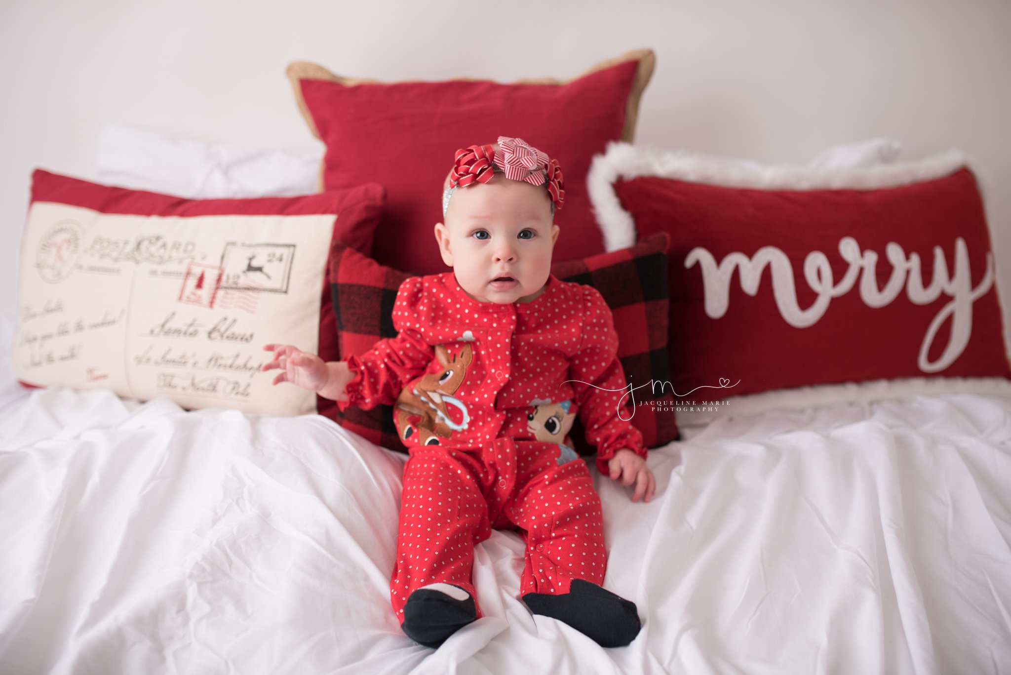 Jacqueline Marie Photography features 6 month baby girl sitting in Christmas pajamas for her portrait session in Columbus Ohio
