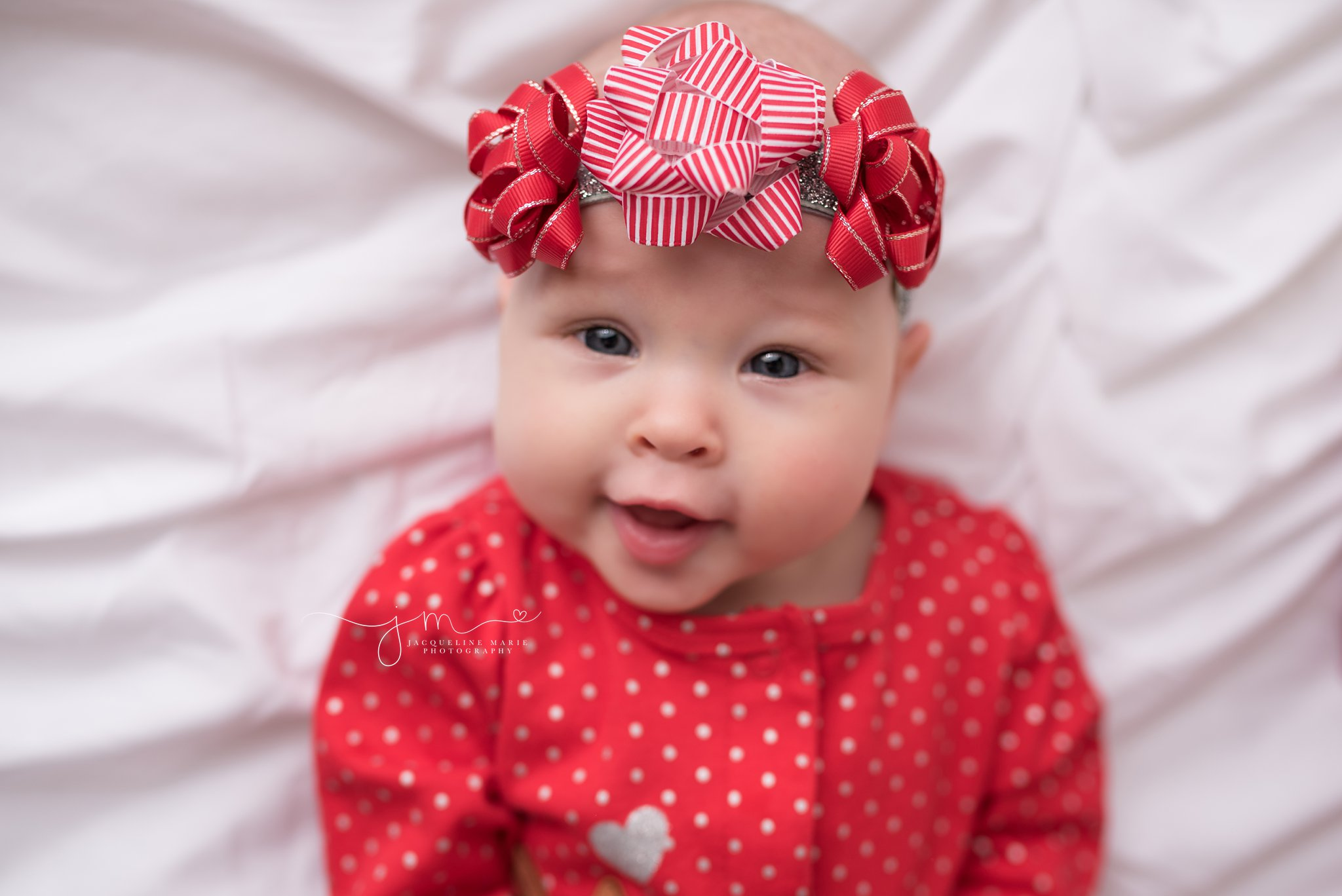 Columbus Ohio baby photographer features portrait of baby girl in Christmas headband with bows