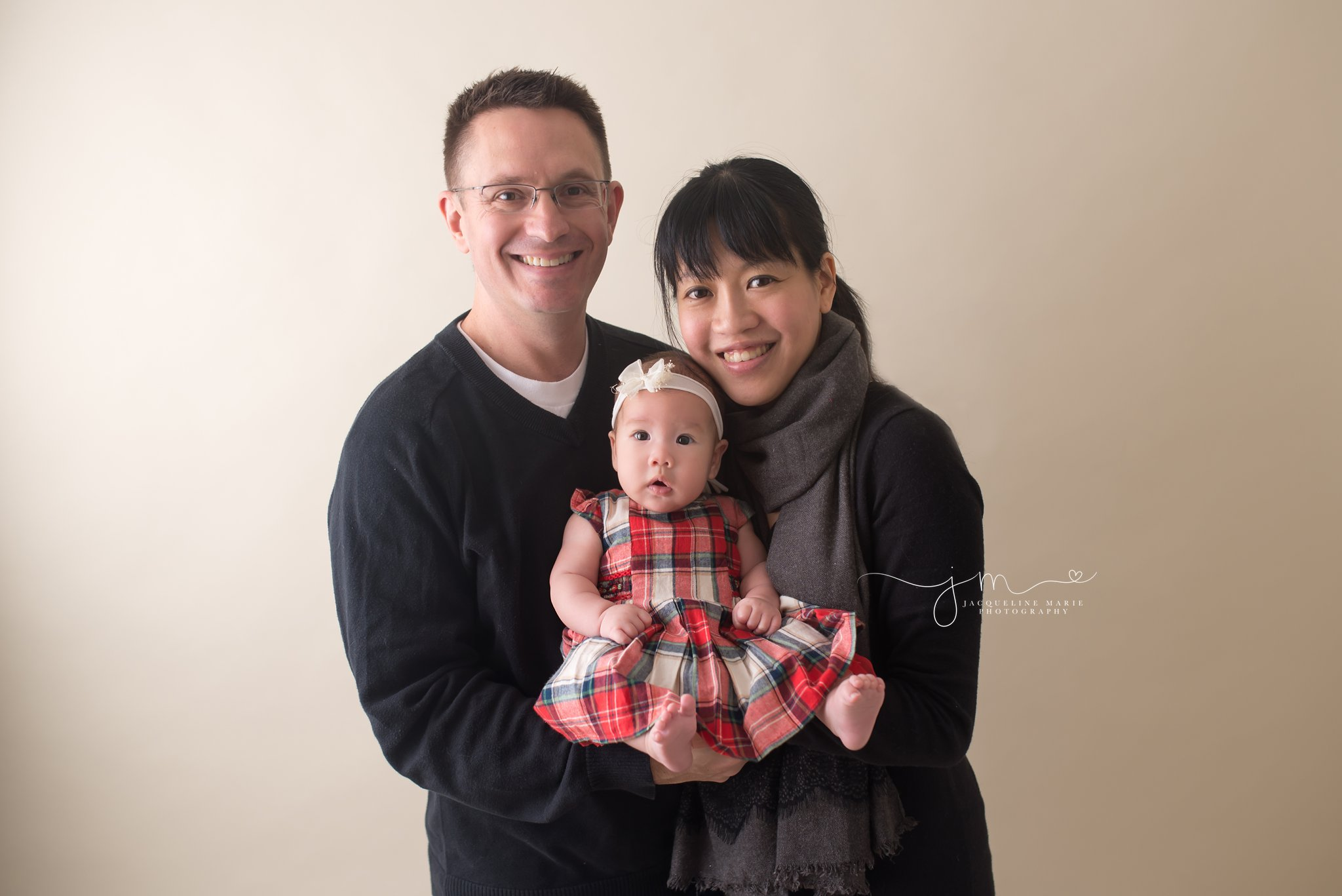 Mother and father hold 3 month old baby girl as she wears her Christmas dress for photography portrait session in Columbus Ohio