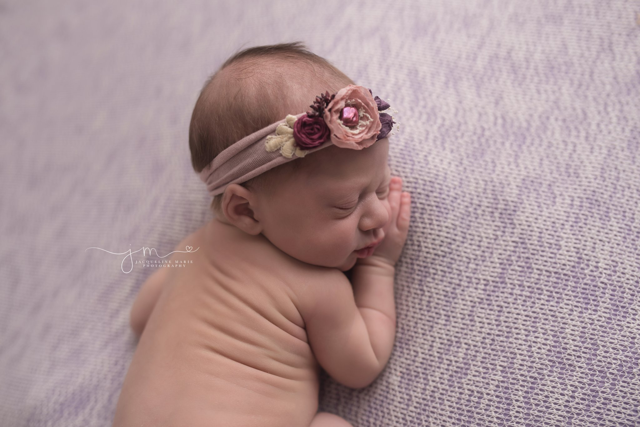 Newborn photography portrait features 9 day old baby girl wearing pink and purple headband with focus on facial features in Columbus Ohio