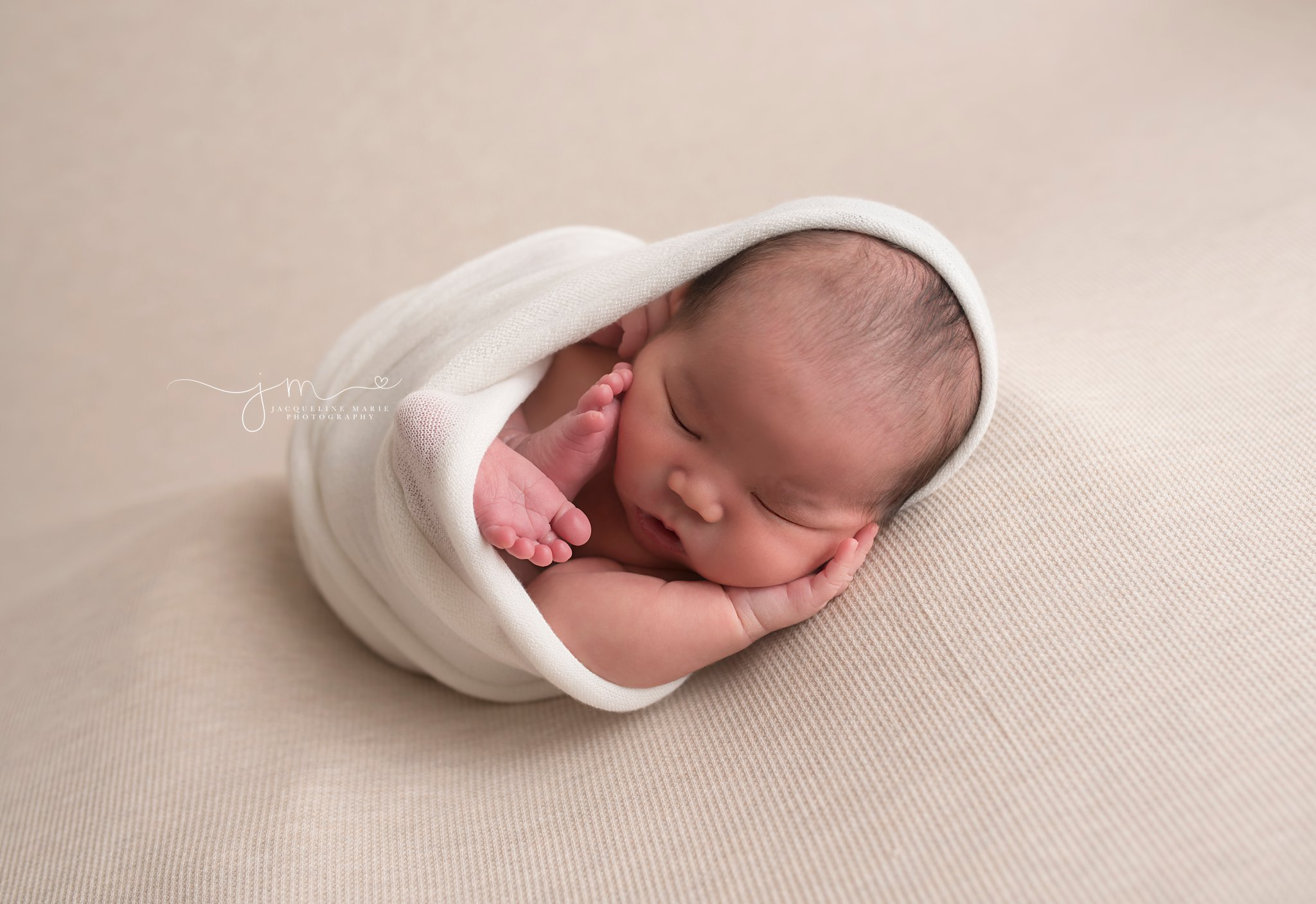 Jacqueline Marie photography studio features newborn swaddled in cream wrap for 9 day old session in Columbus Ohio