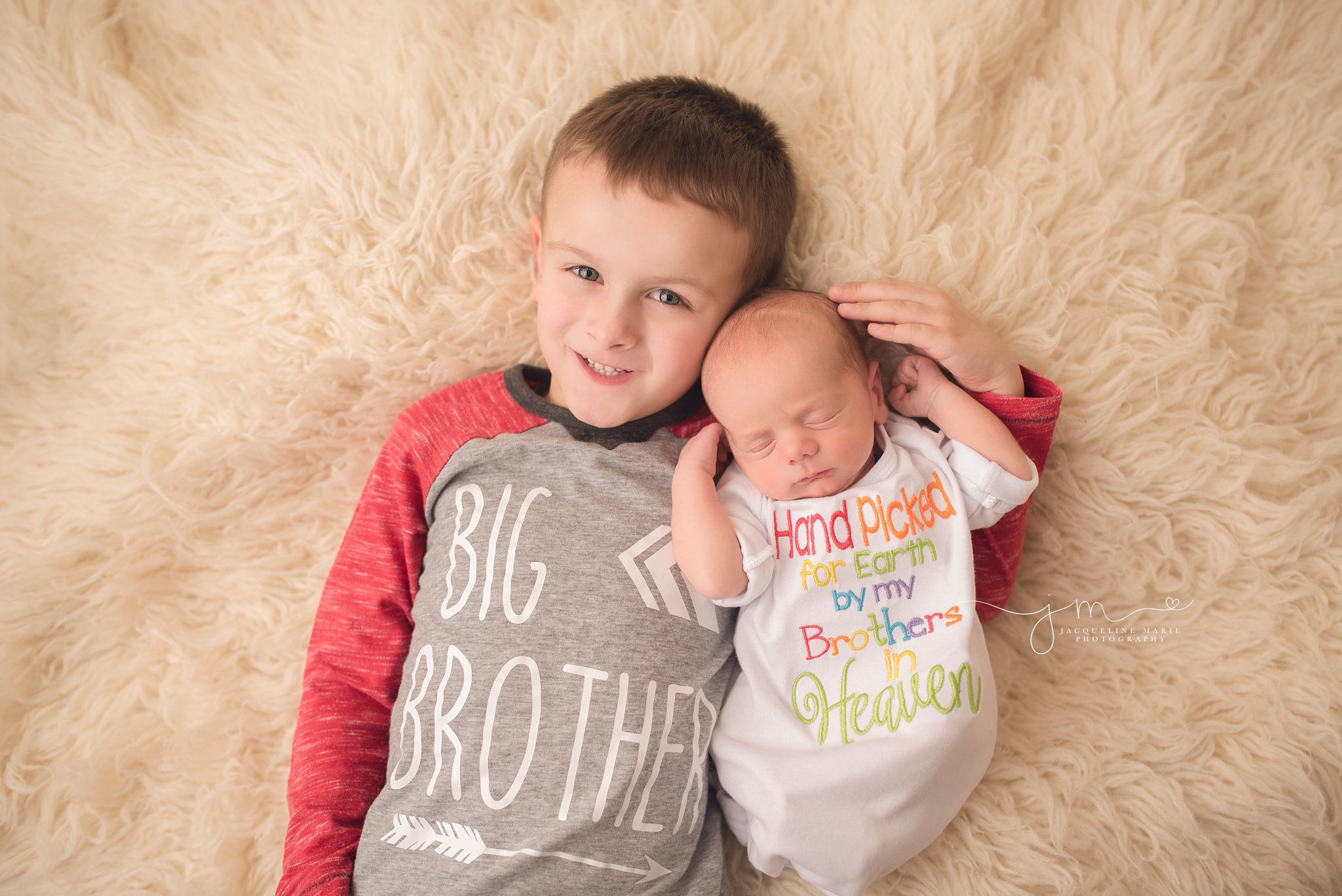big brother poses with newborn baby sibling for newborn pictures in columbus ohio