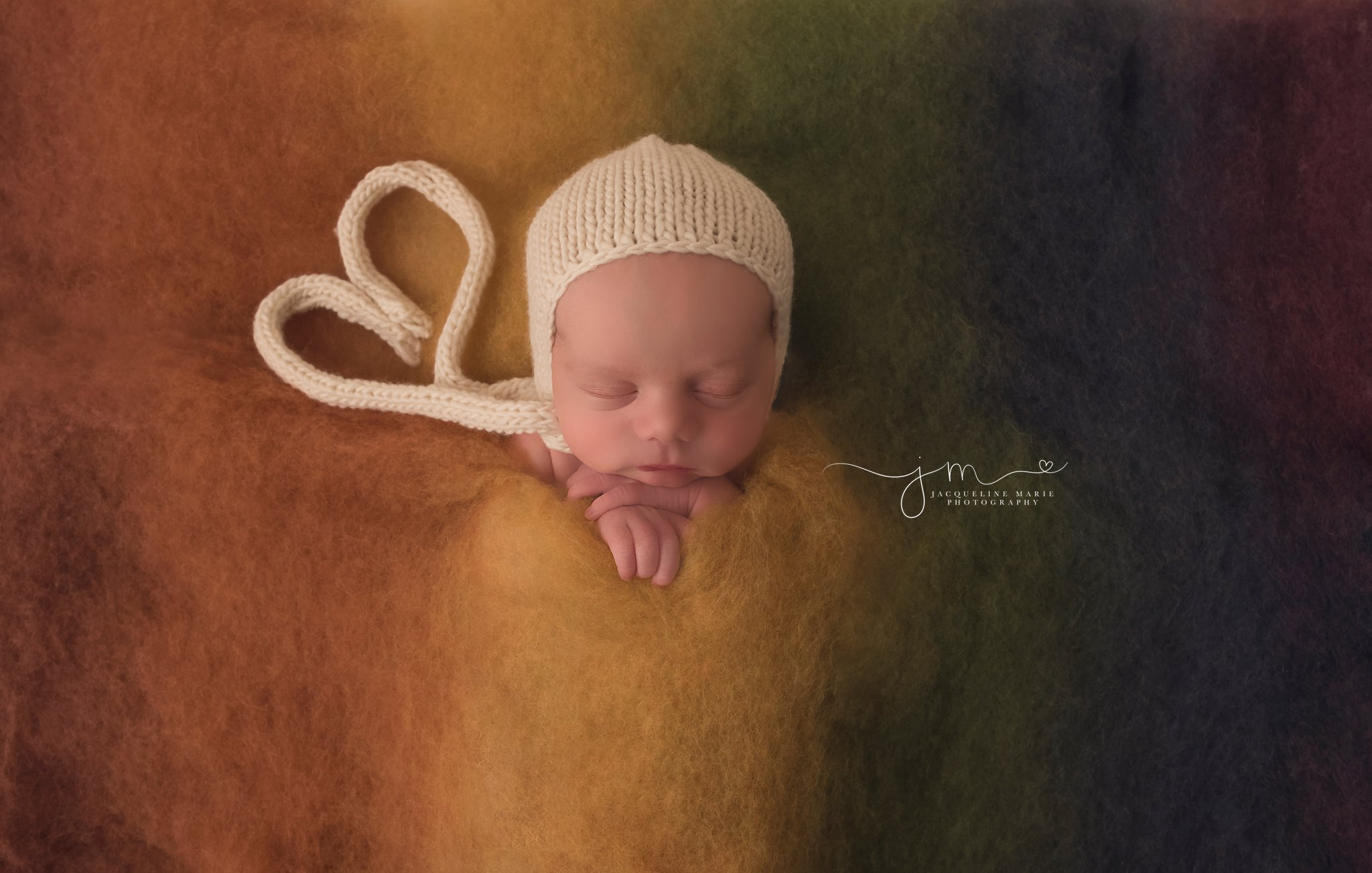 11 day old newborn rainbow baby snuggled in rainbow fluff for newborn pictures at Jacqueline Marie Photography studio in columbus ohio