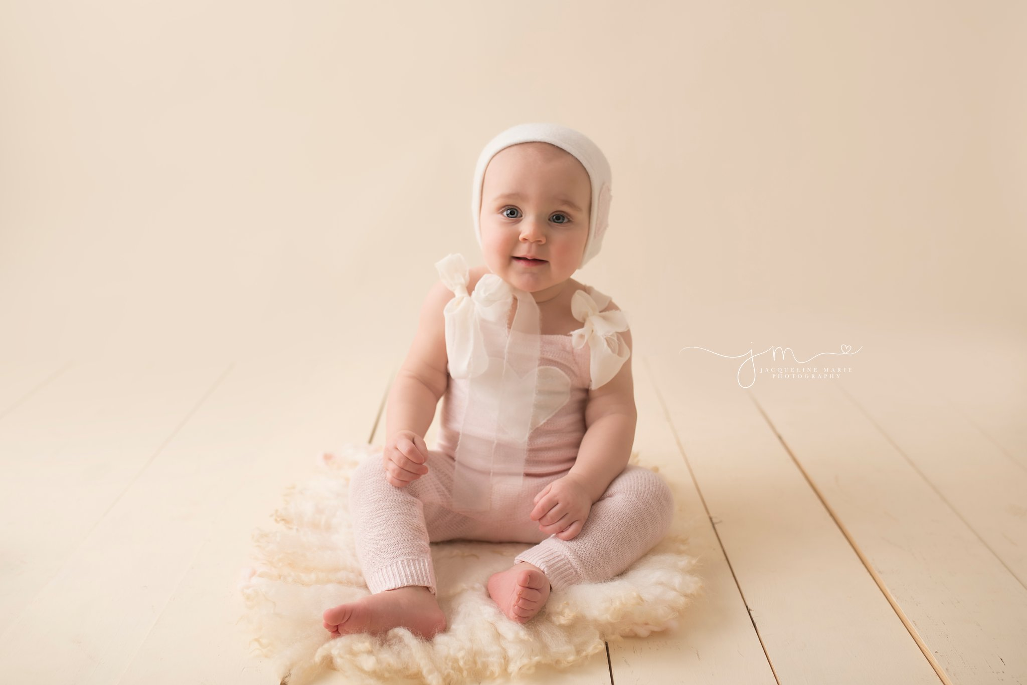columbus ohio one year old wears pink and cream romper for first birthday pictures