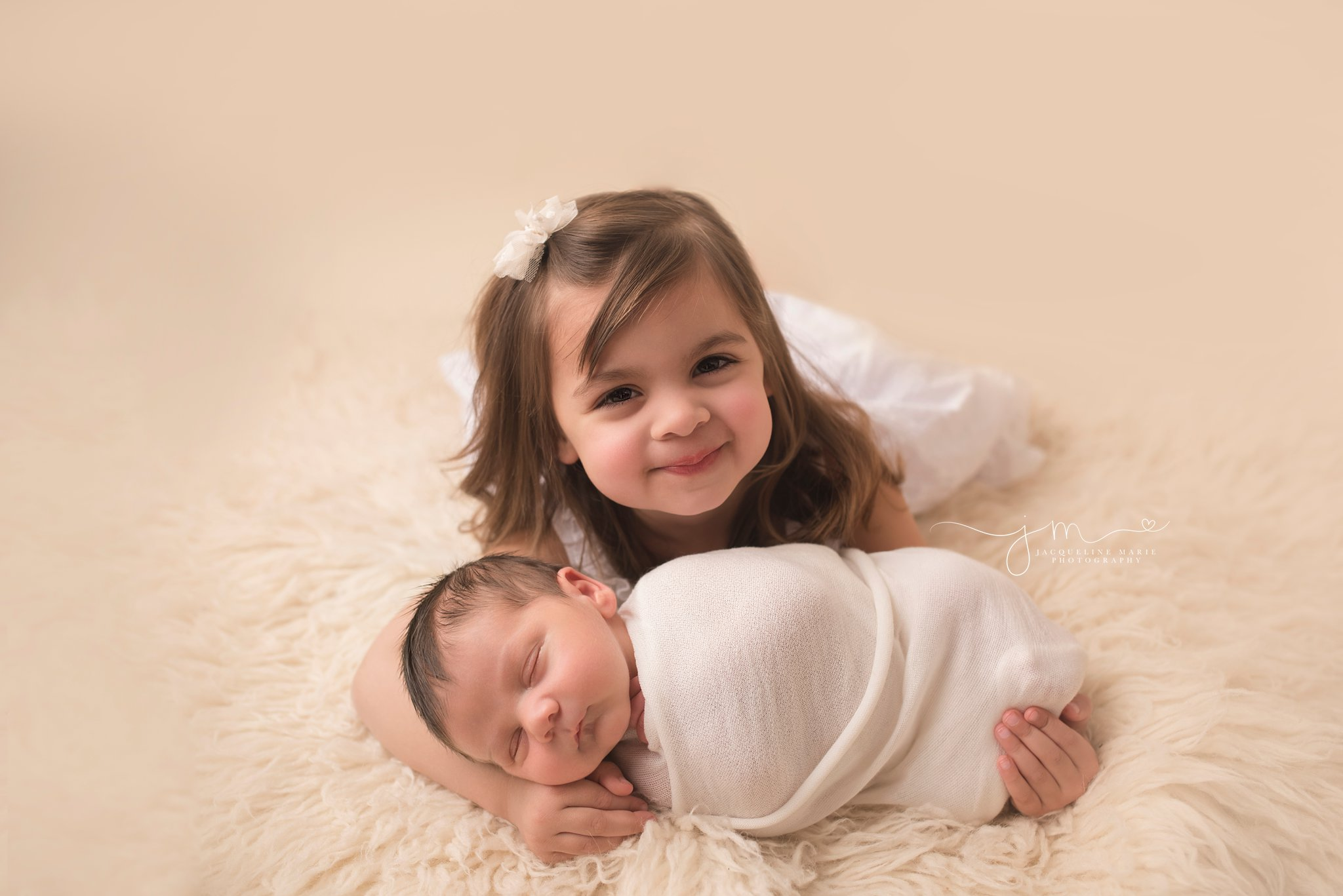 neutral newborn images features newborn baby sleeping and big sister smiling in columbus ohio