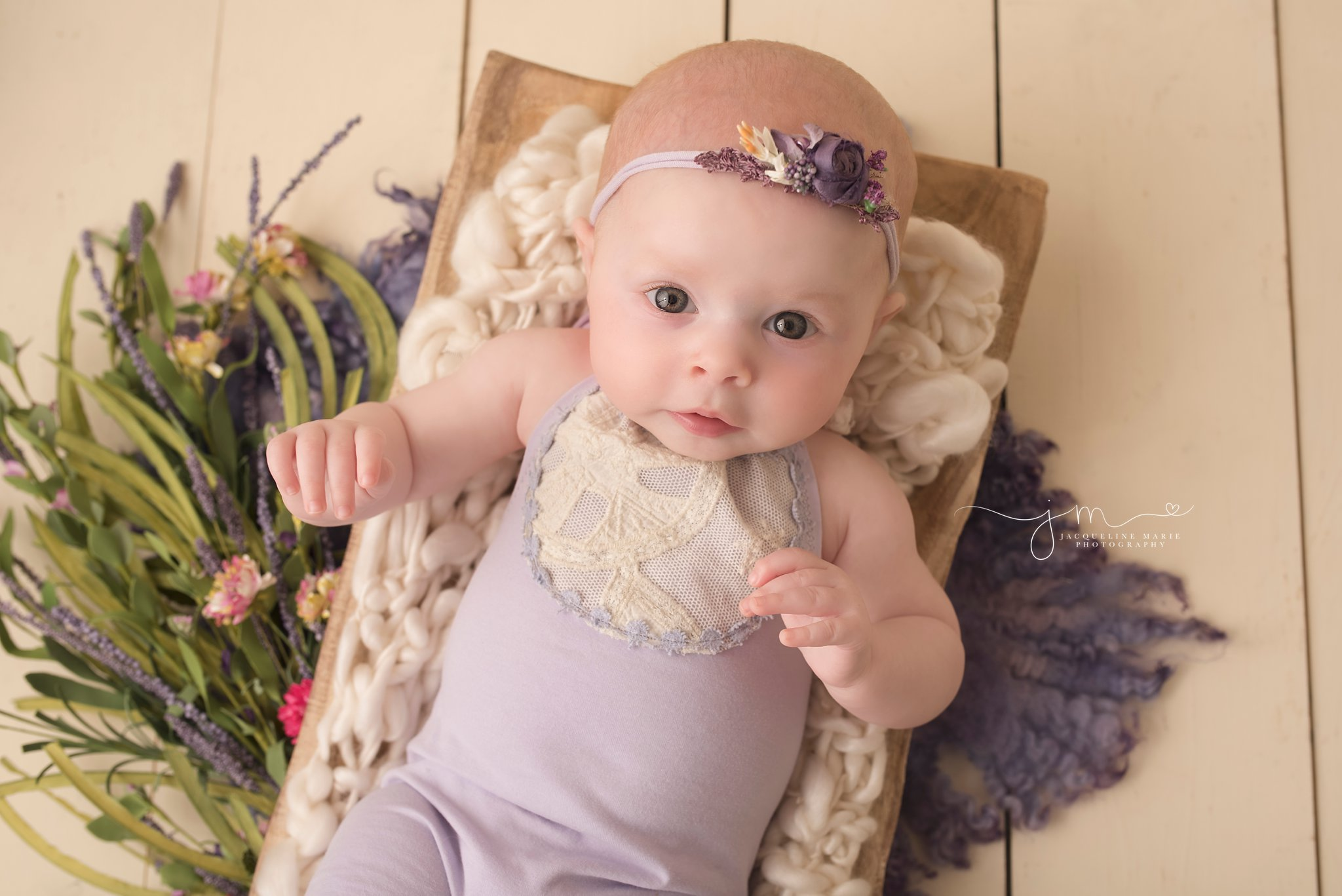 baby girl wears purple romper and matching headband in Columbus ohio for baby pictures