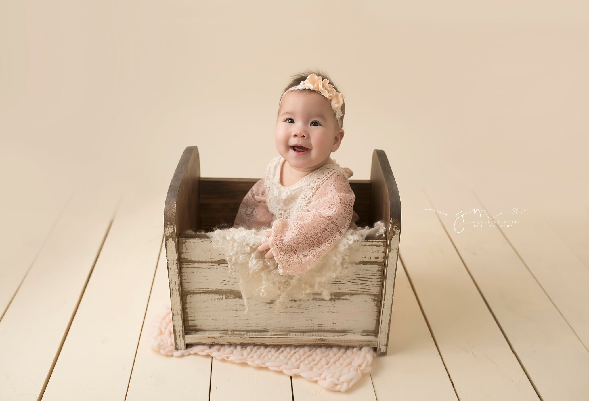 6 month old baby girl from new albany ohio wears pink romper while sitting in cream wood bed for milestone pictures at jacqueline marie photography