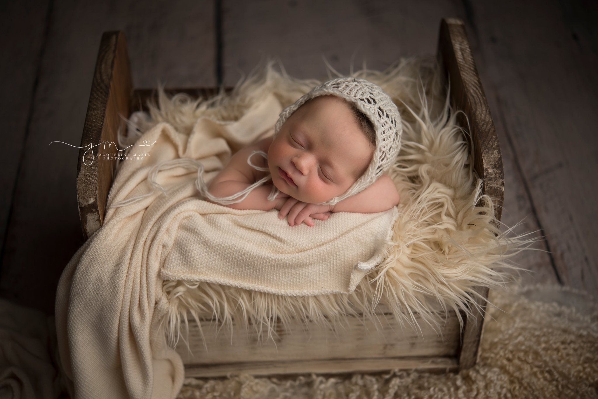 columbus ohio newborn photographer poses newborn baby in wood bed for newborn mentoring session with Photograpy by axis design in toccoa georgia