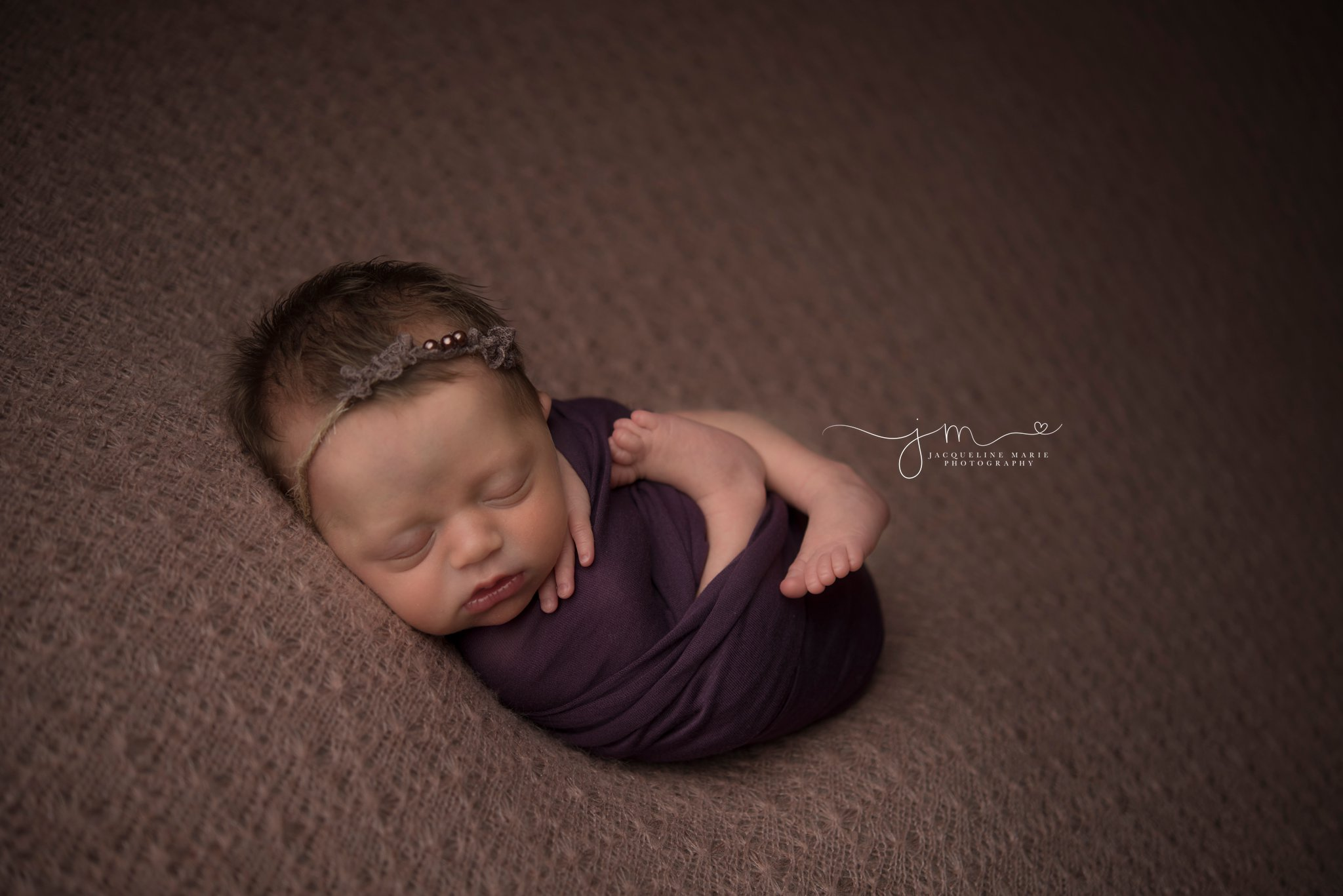 5 day old newborn baby girl is swaddled in purple wrap for newborn photography portraits by columbus ohio newborn photographer jacqueline marie photography