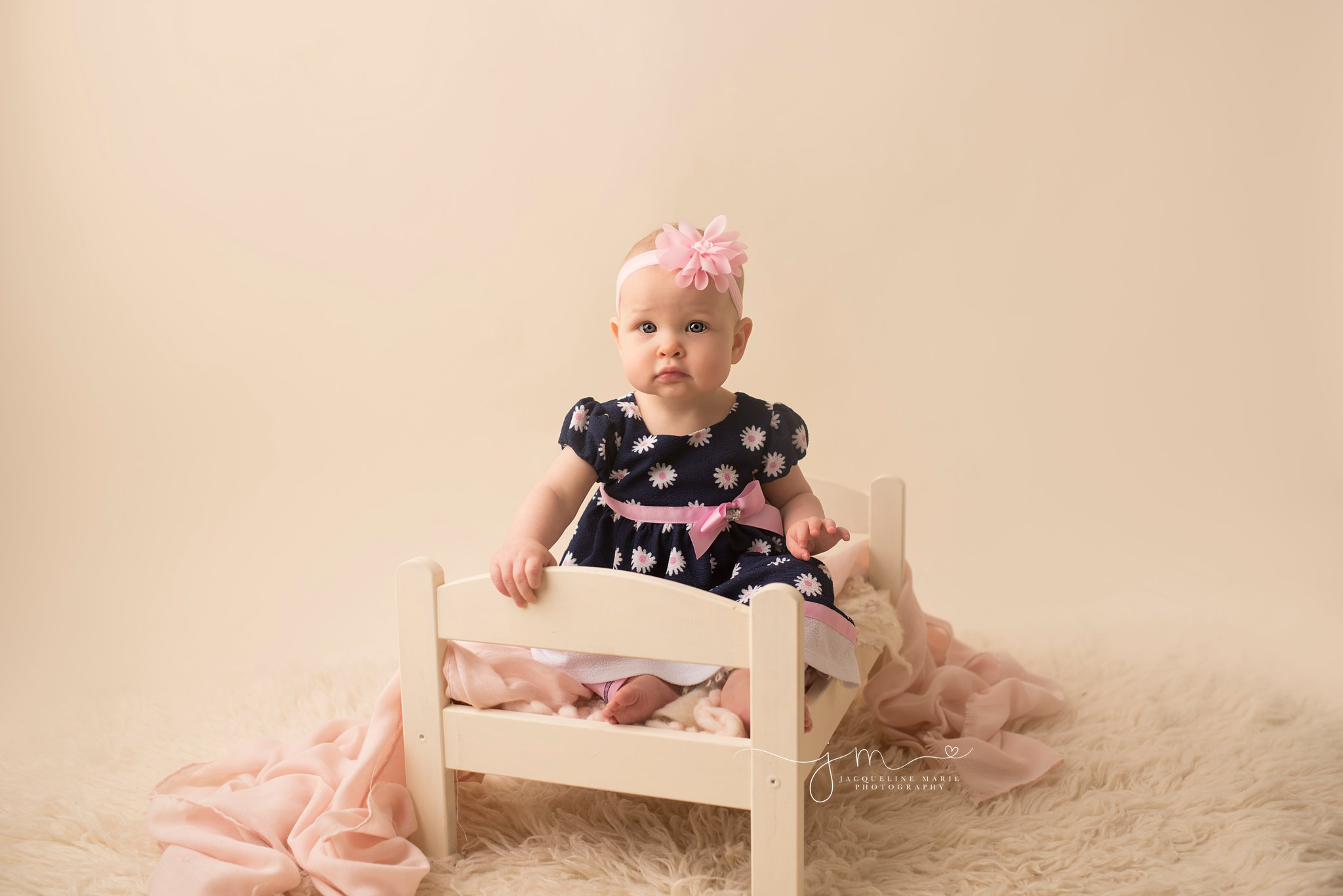 9 month old bay girl sits on cream bed for baby milestone pictures in columbus ohio