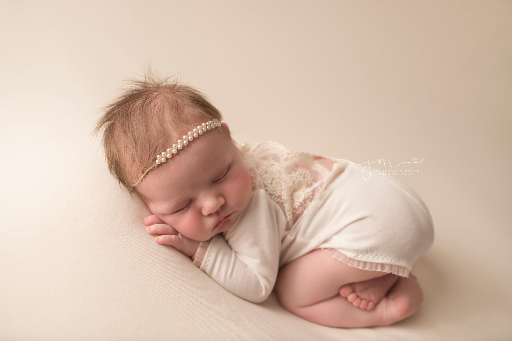 newborn baby girl is sleeping in cream romper at 12 days old for newborn photography portraits in columbus ohio