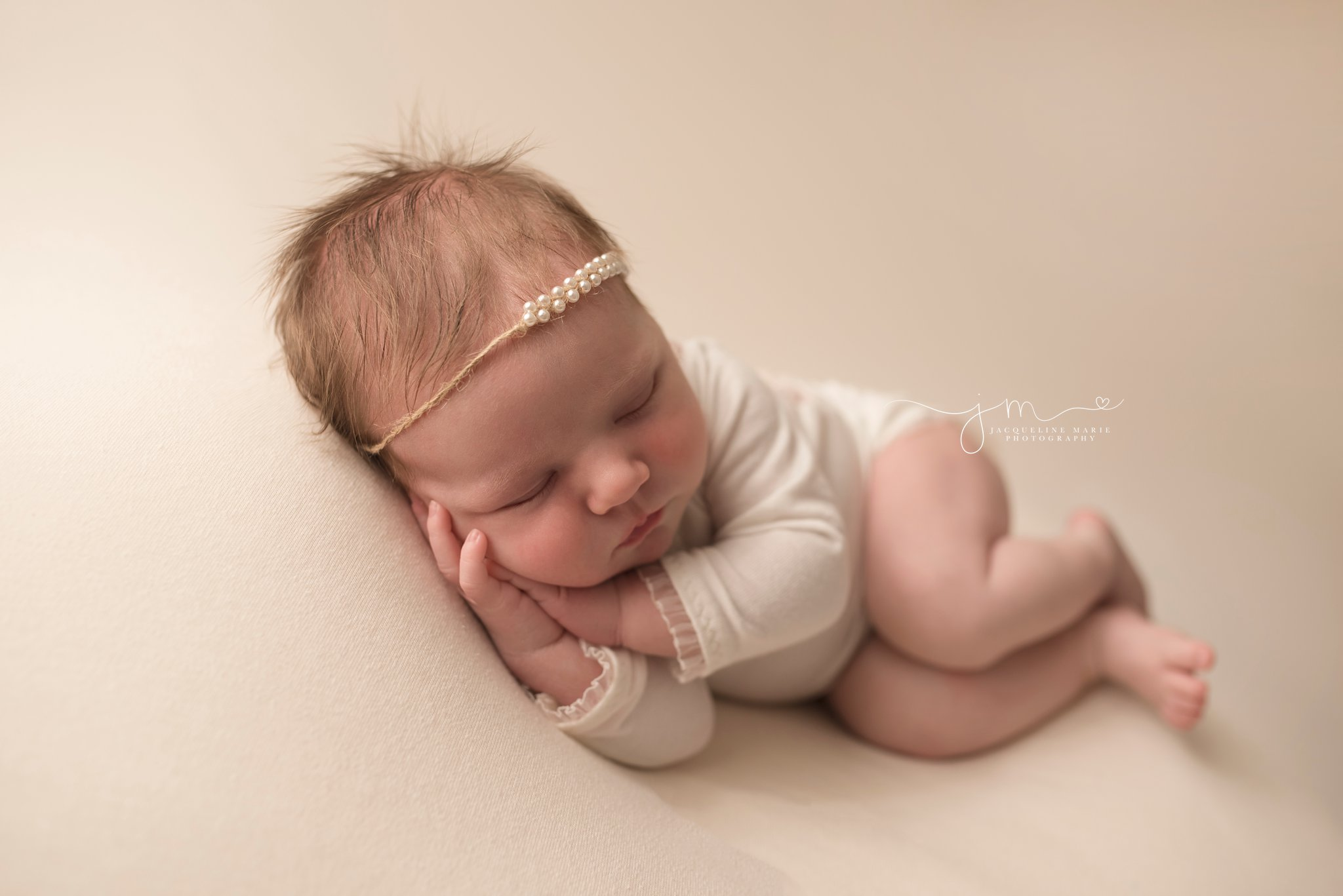 columbus ohio newborn photographer features baby girl wearing pearl headband while sleeping
