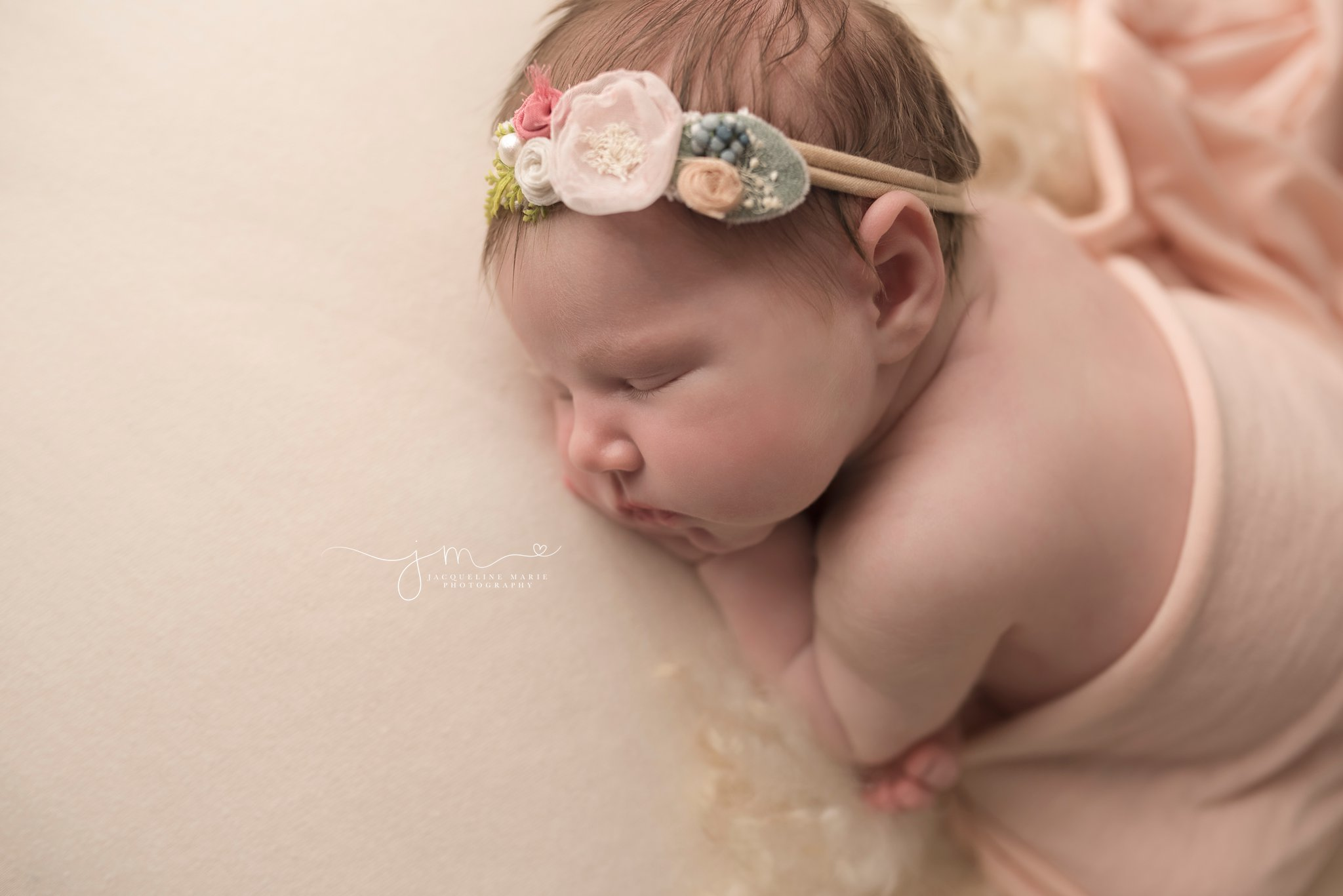 newborn photography portrait features baby girl wearing pastel headband and pink wrap in columbus ohio