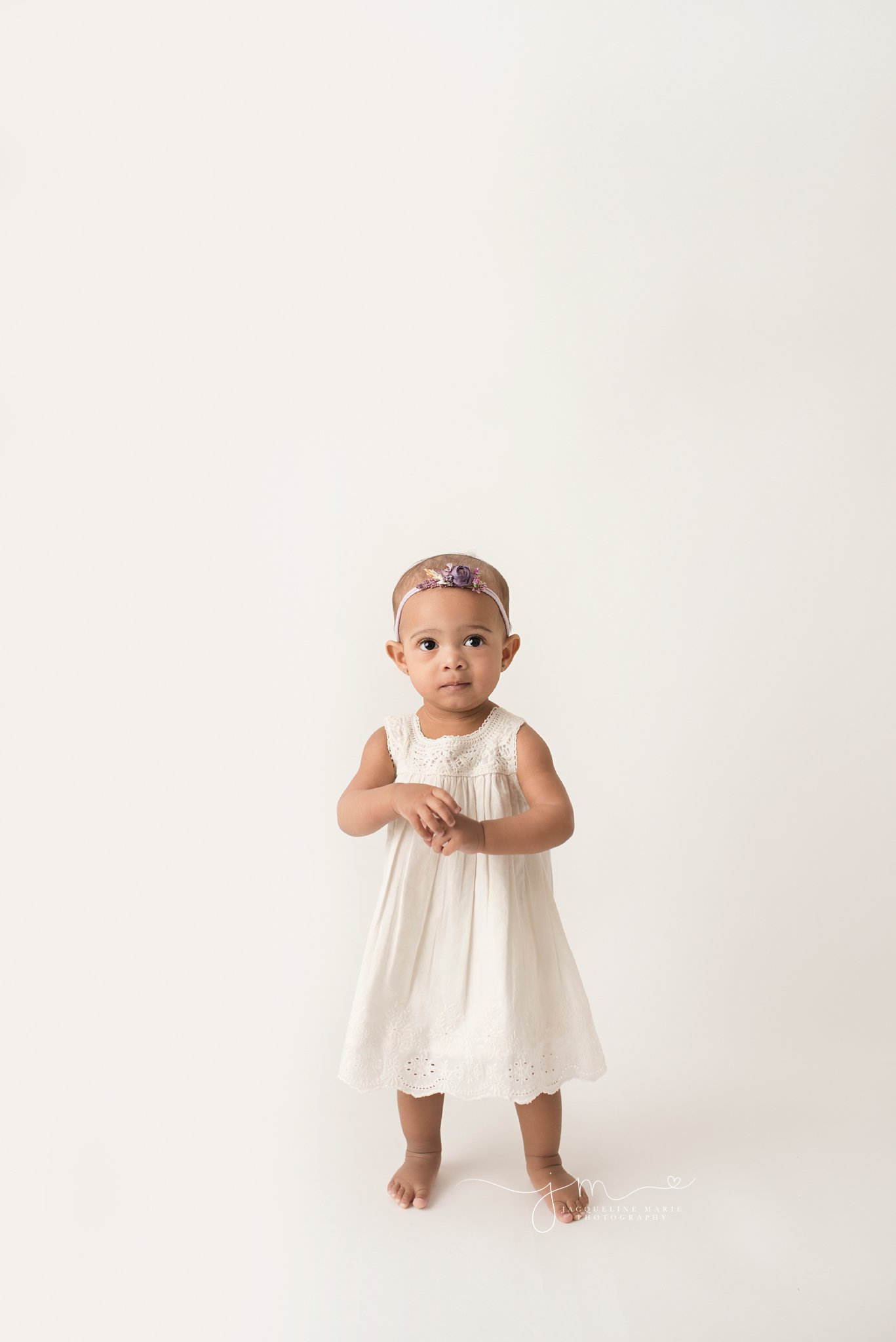 columbus ohio 1 year old wears white dress for while standing at portrait studio for first birthday pictures