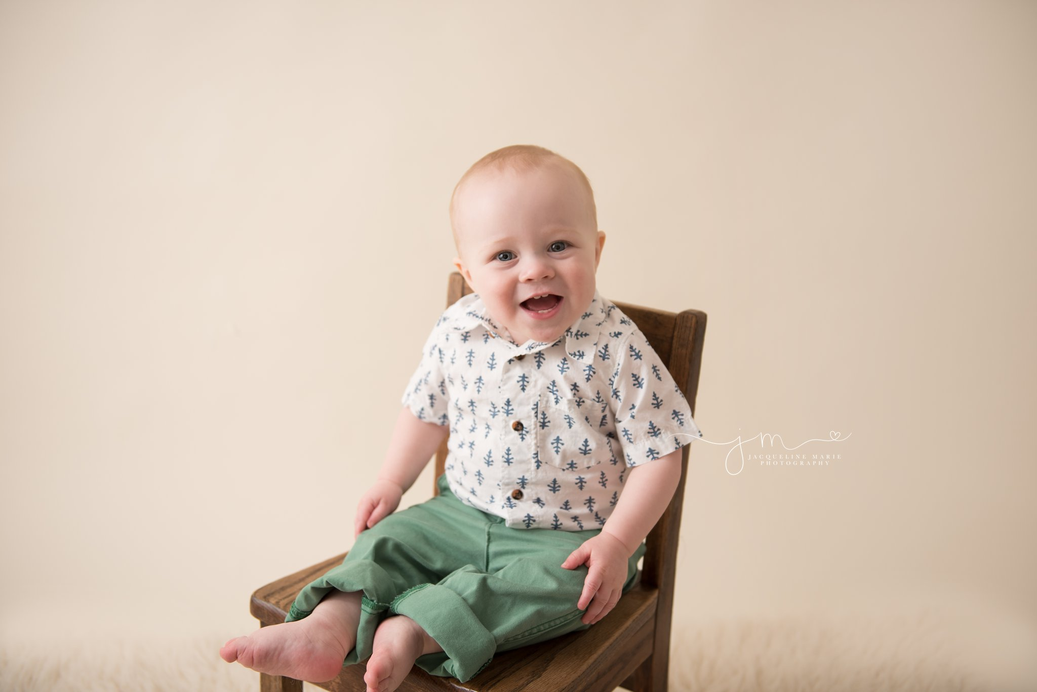 columbus ohio 1 year old smiles while wearing green pants and sitting on wooden chair for first birthday pictures