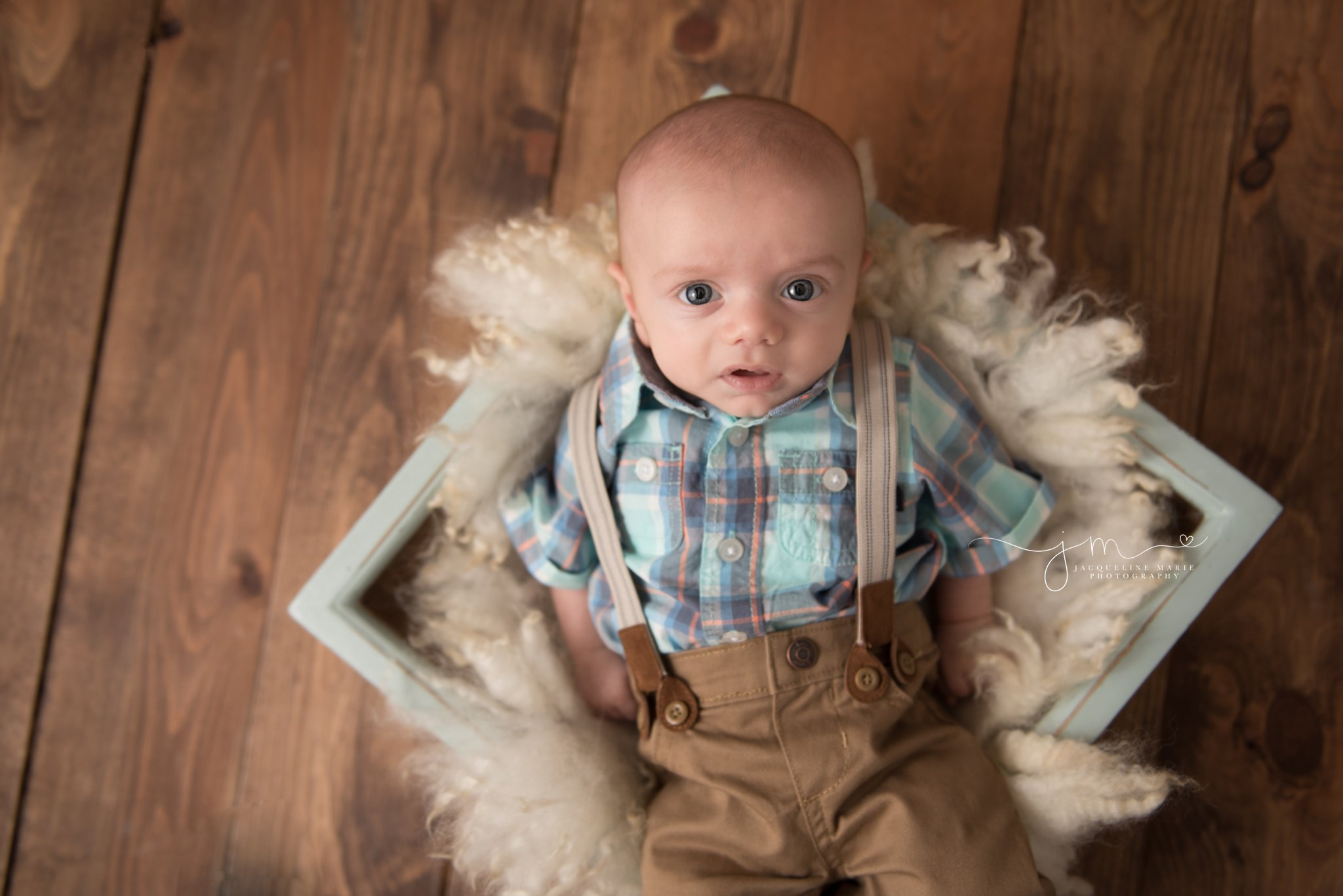 3 month old baby boy with blue eyes is posed in blue wooden prop on wood floor in columbus ohio at jacqueline marie photography studio