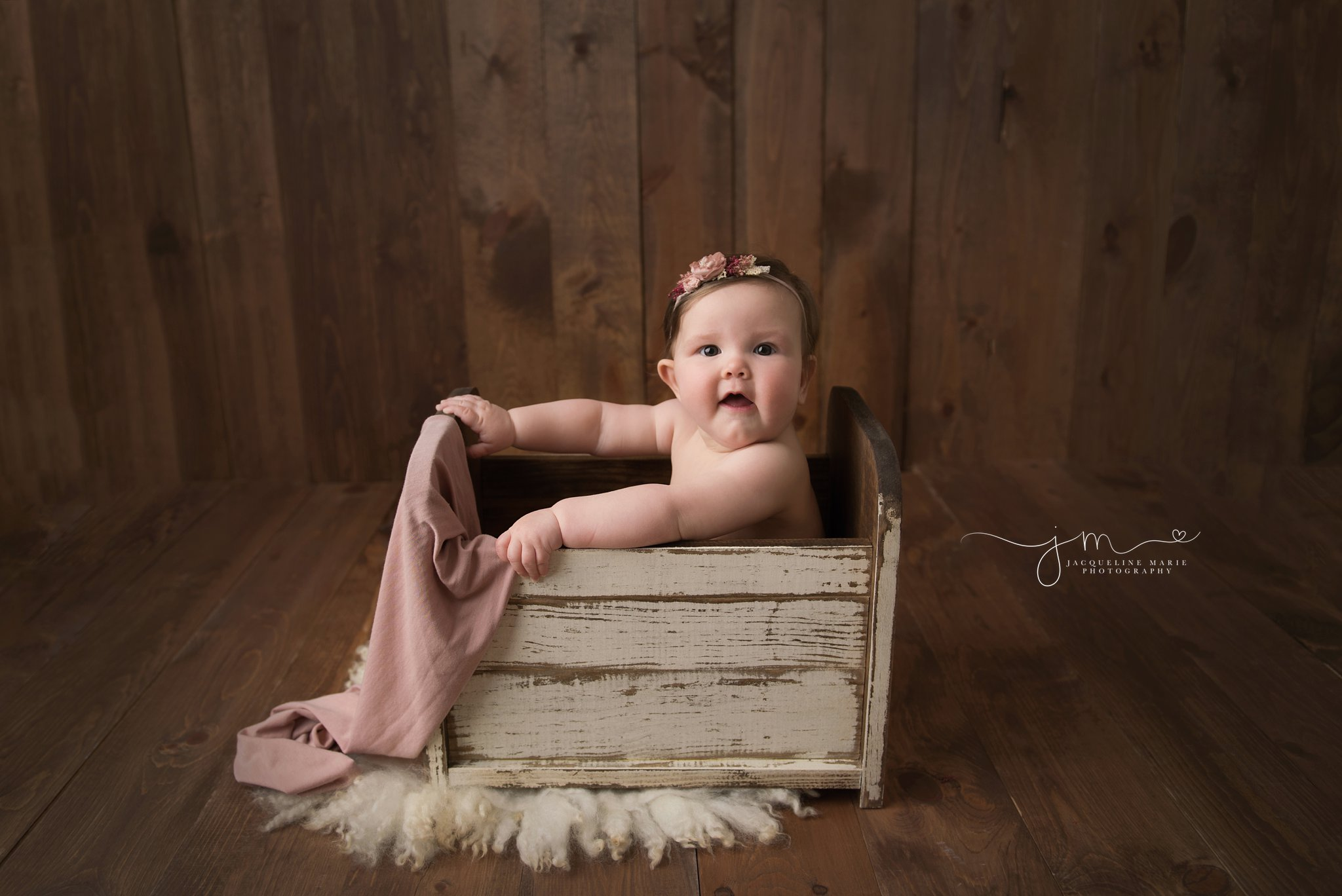 6 month old baby girl wears pink floral headband and sits in white wooden bed for milestone baby pictures in columbus ohio