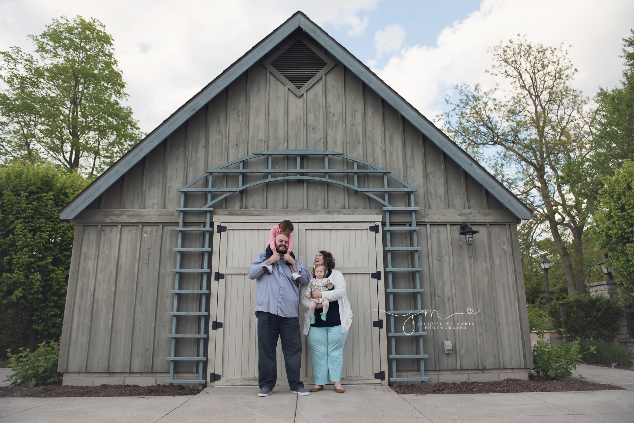 columbus ohio family photographer features mother and father holding son and daughter for adoption pictures in front of barn at franklin park conservatory