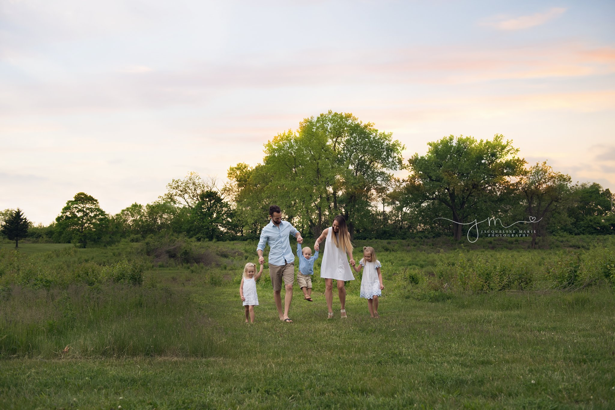 columbus ohio family of five walks at sunset in a park holding hands for family photography session with jacqueline marie photography