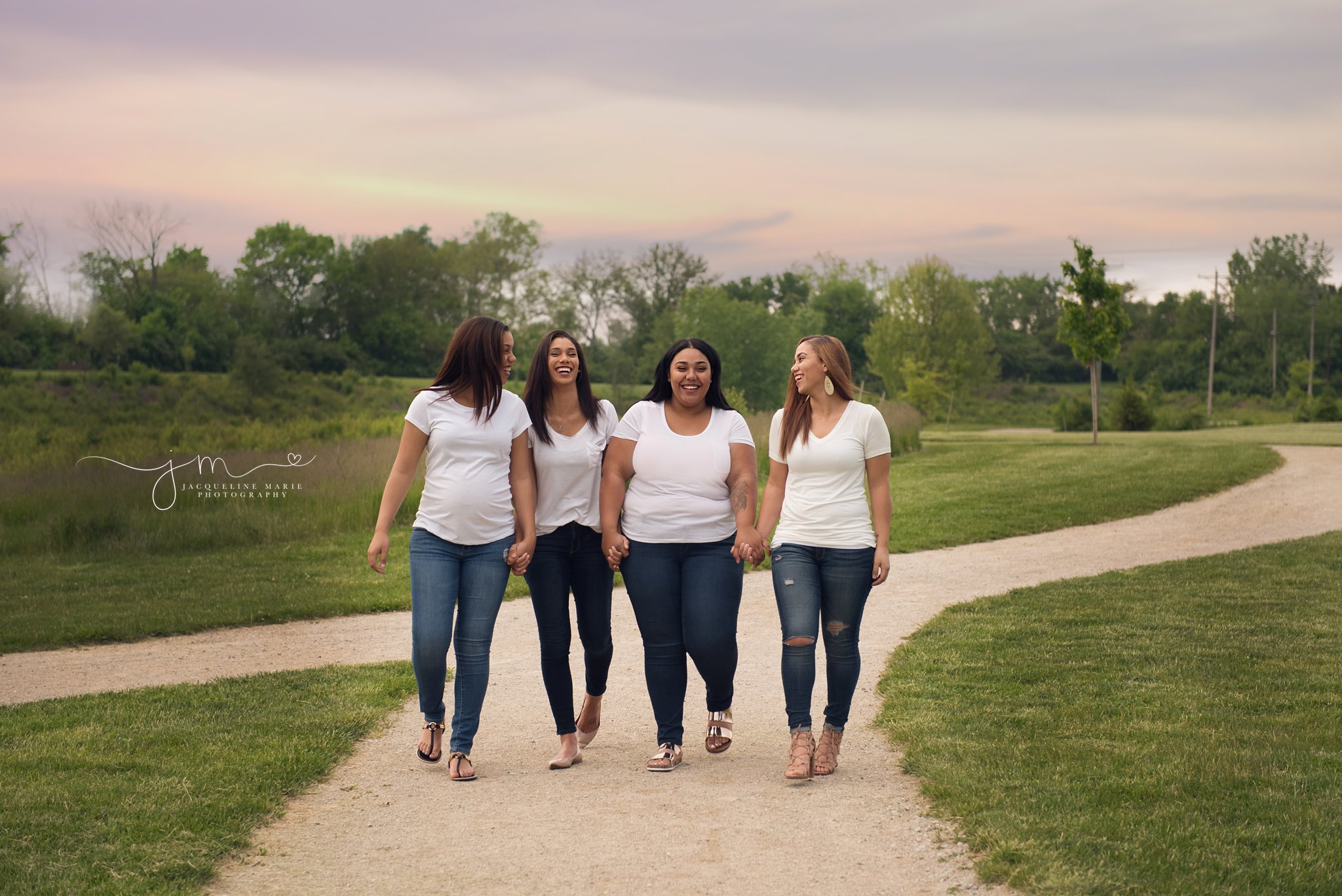 four sisters walk together laughing and holding hands in columbus ohio for family photography pictures