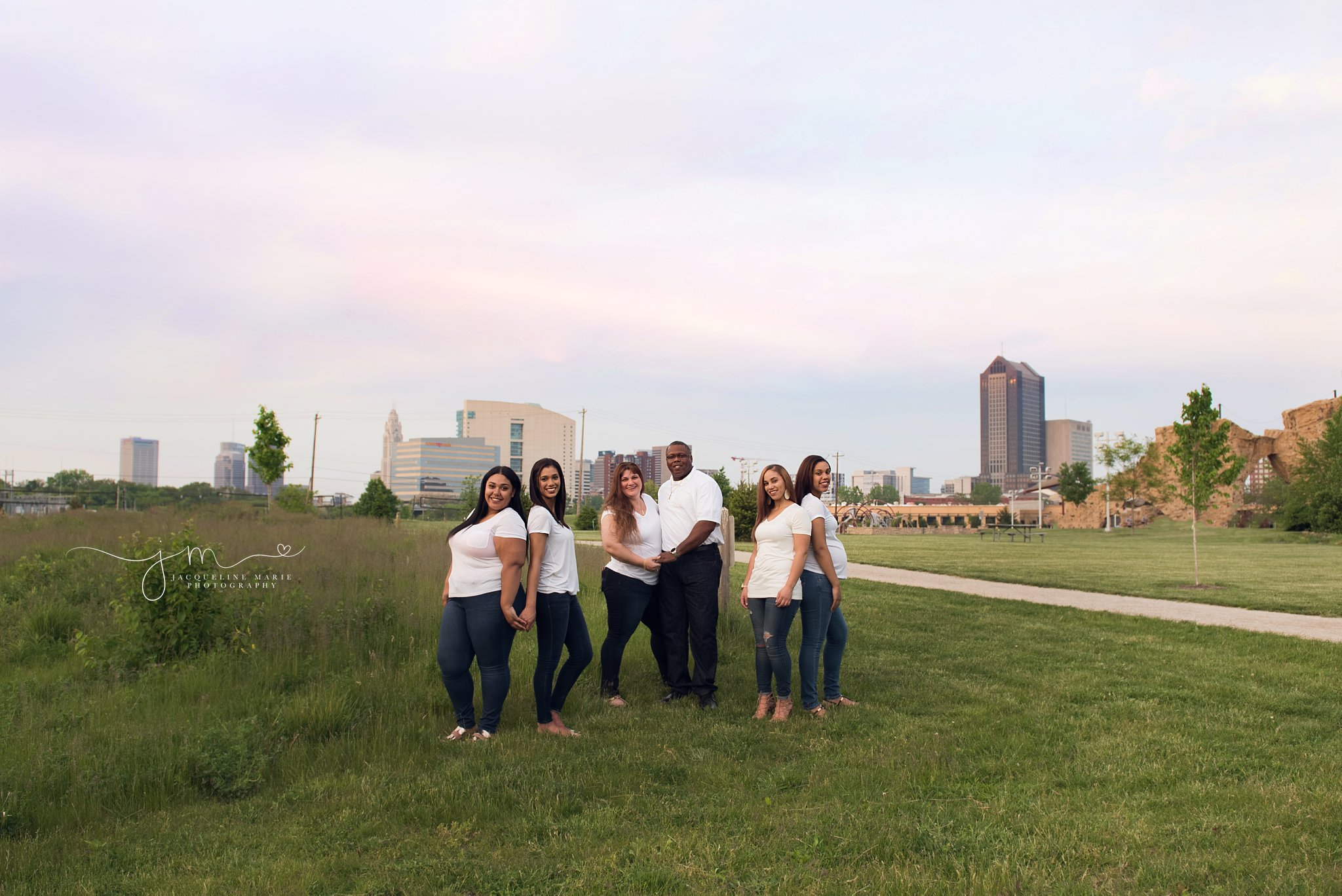 family photographer in Columbus ohio features family poses with columbus skyline