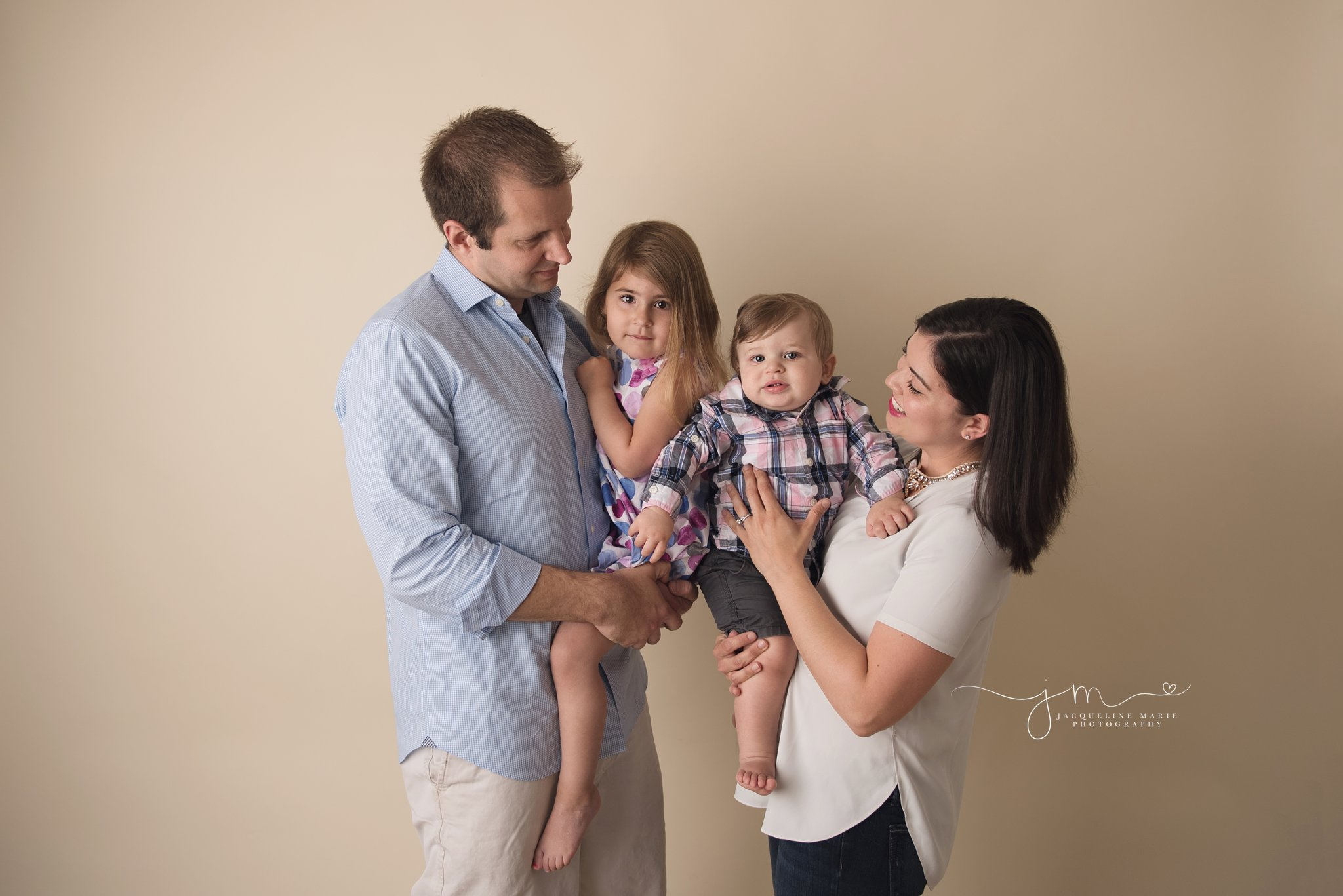 family of four portrait features mother and father holding son and daughter in columbus ohio