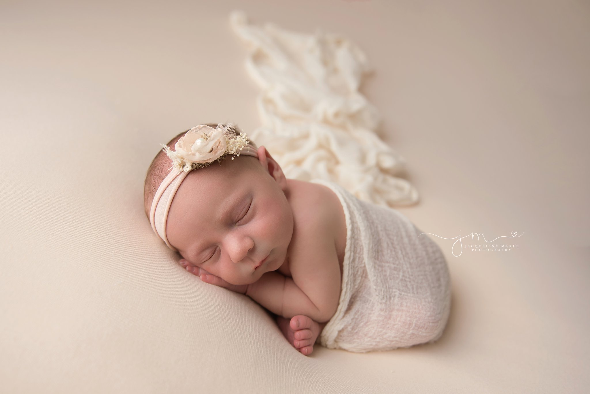 1 week old newborn baby girl is wrapped in cream wrap and matching headband for newborn portraits in columbus ohio