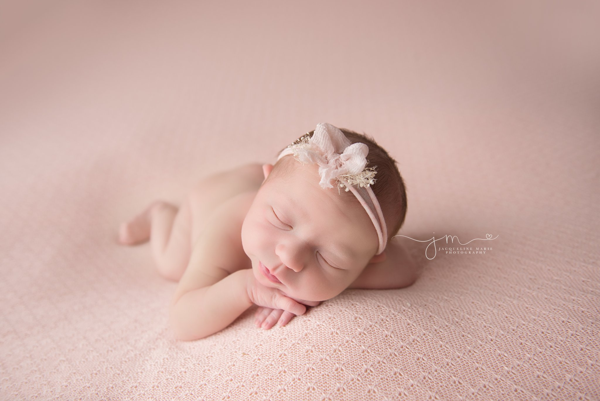 columbus ohio newborn baby girl lays on pink knitted blanket and wears headband with pink bow for newborn photography portraits