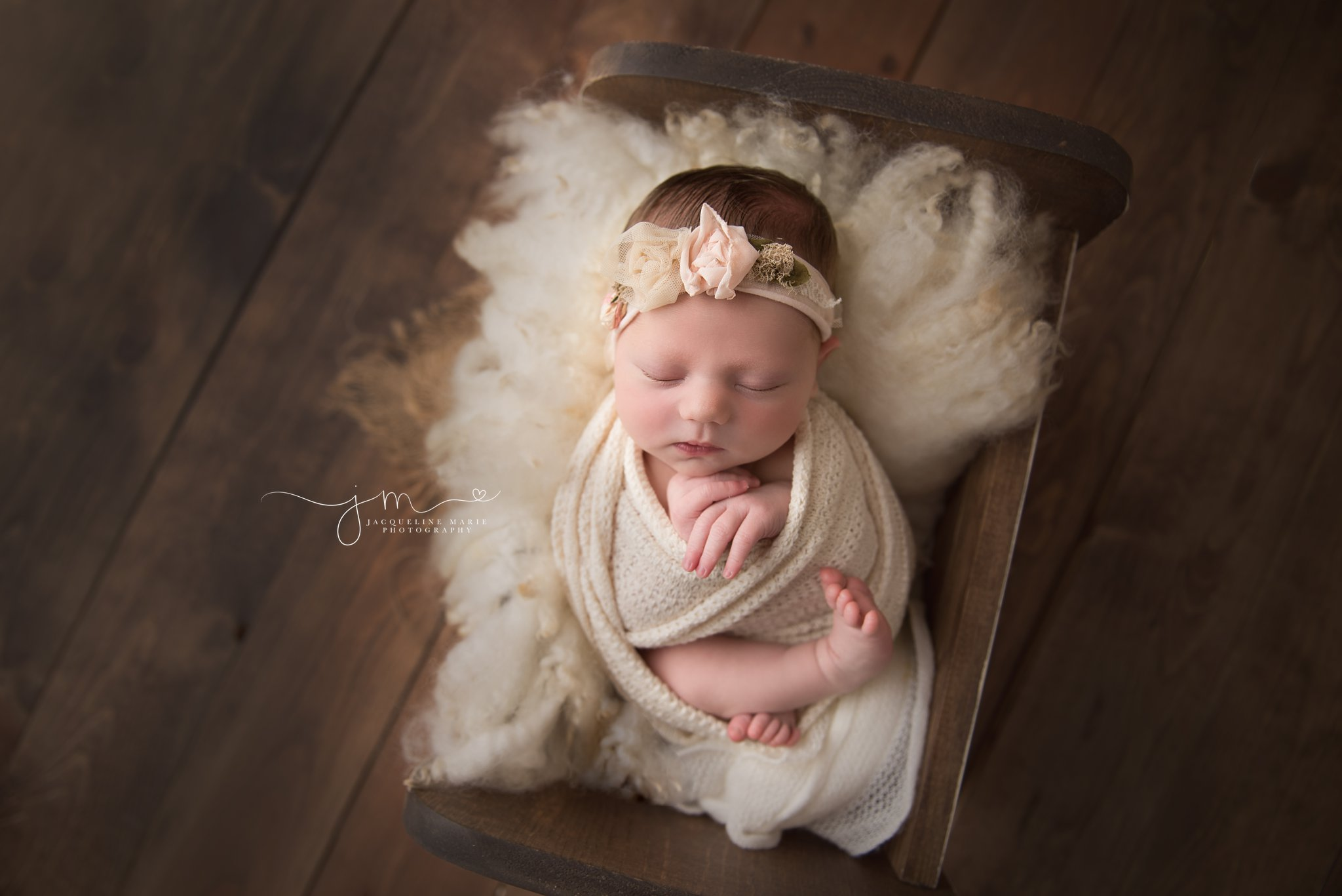 columbus ohio newborn baby girl is swaddled in cream wrap and laying in wood bed for newborn photography portraits at jacqueline marie photography studio