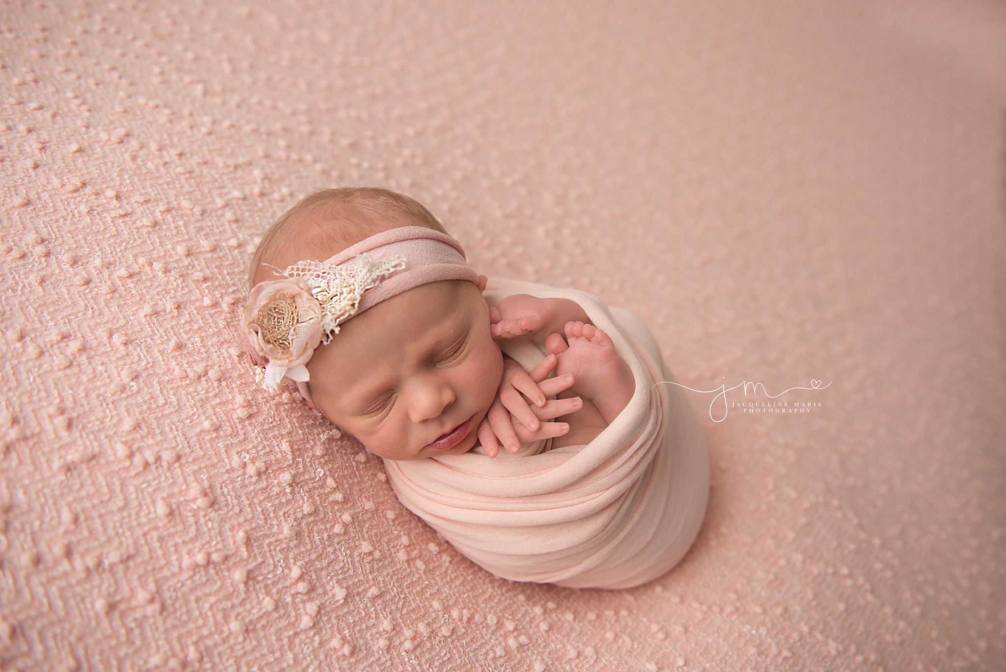 columbus ohio newborn photographer features image of newborn baby girl swaddled in pink wrap and matching headband