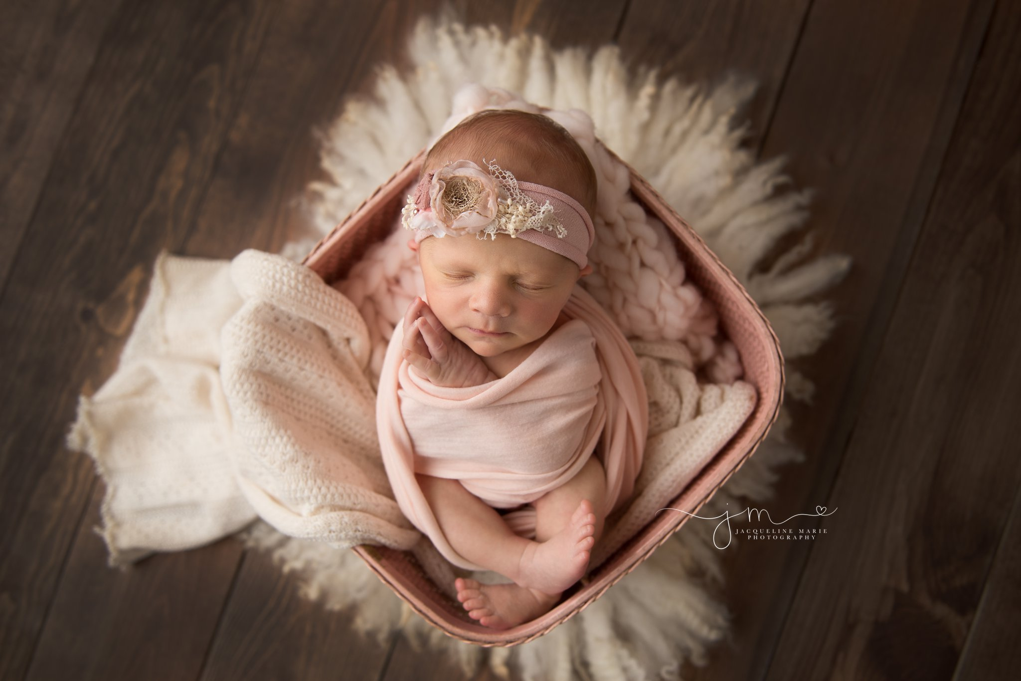 columbus ohio newborn baby girl folds hands near face while swaddled in pink basket for newborn photos