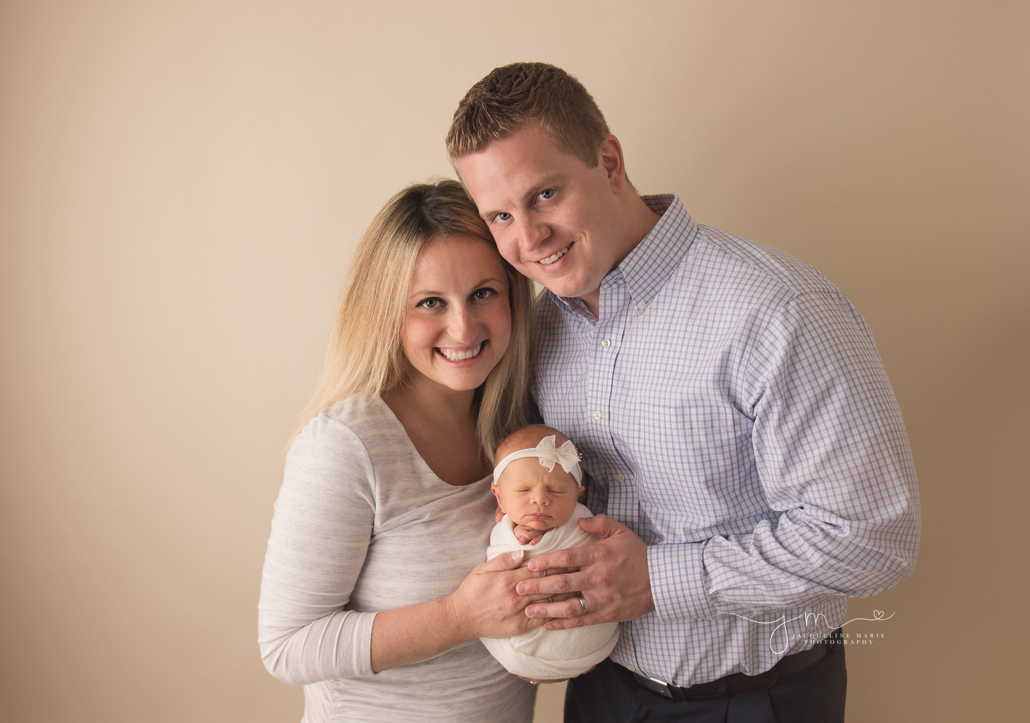 mother and father hold two week old baby girl in columbus ohio for newborn pictures