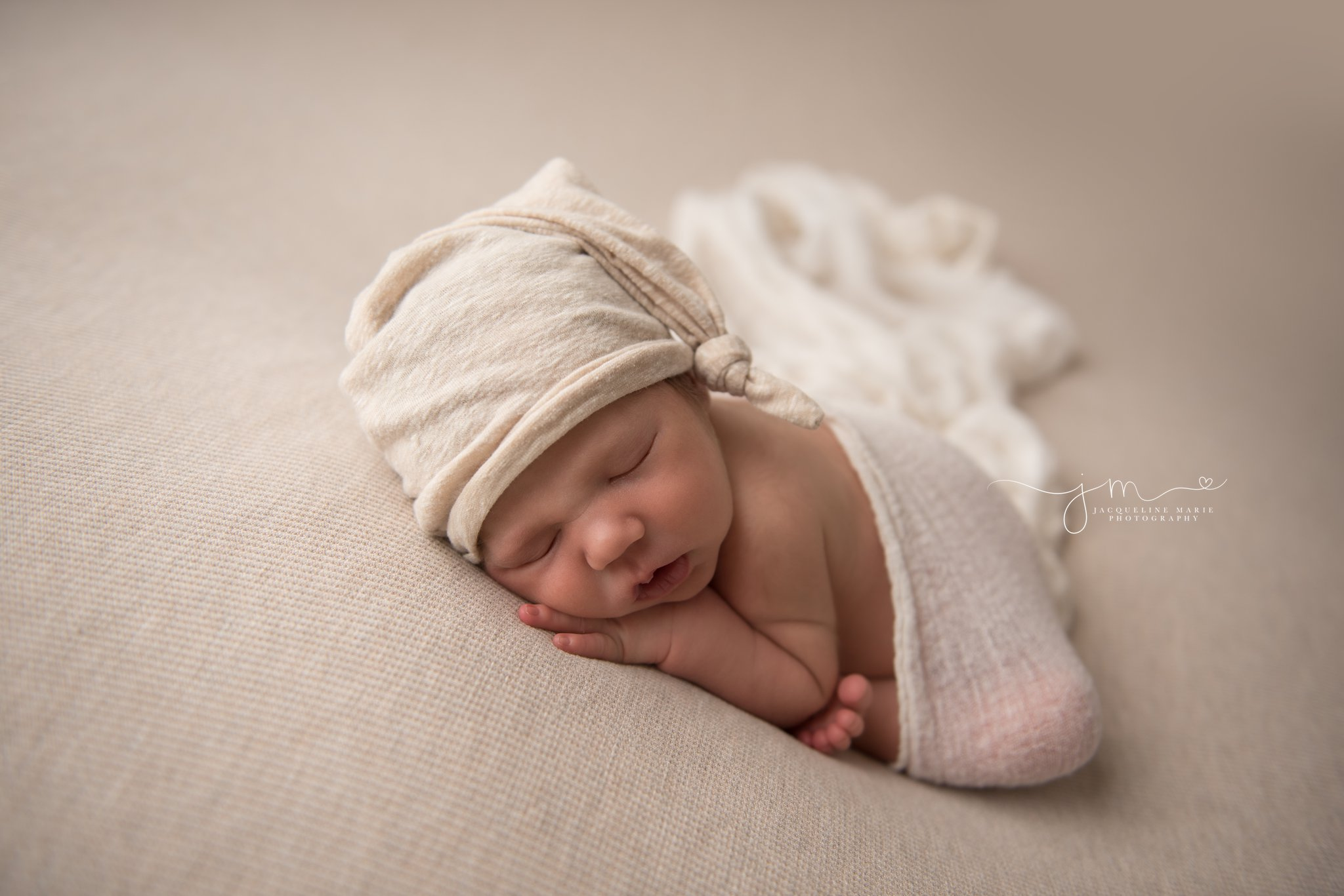 columbus ohio newborn baby boy wears cream hat and is swaddled in cream wrap at jacqueline marie photography studio