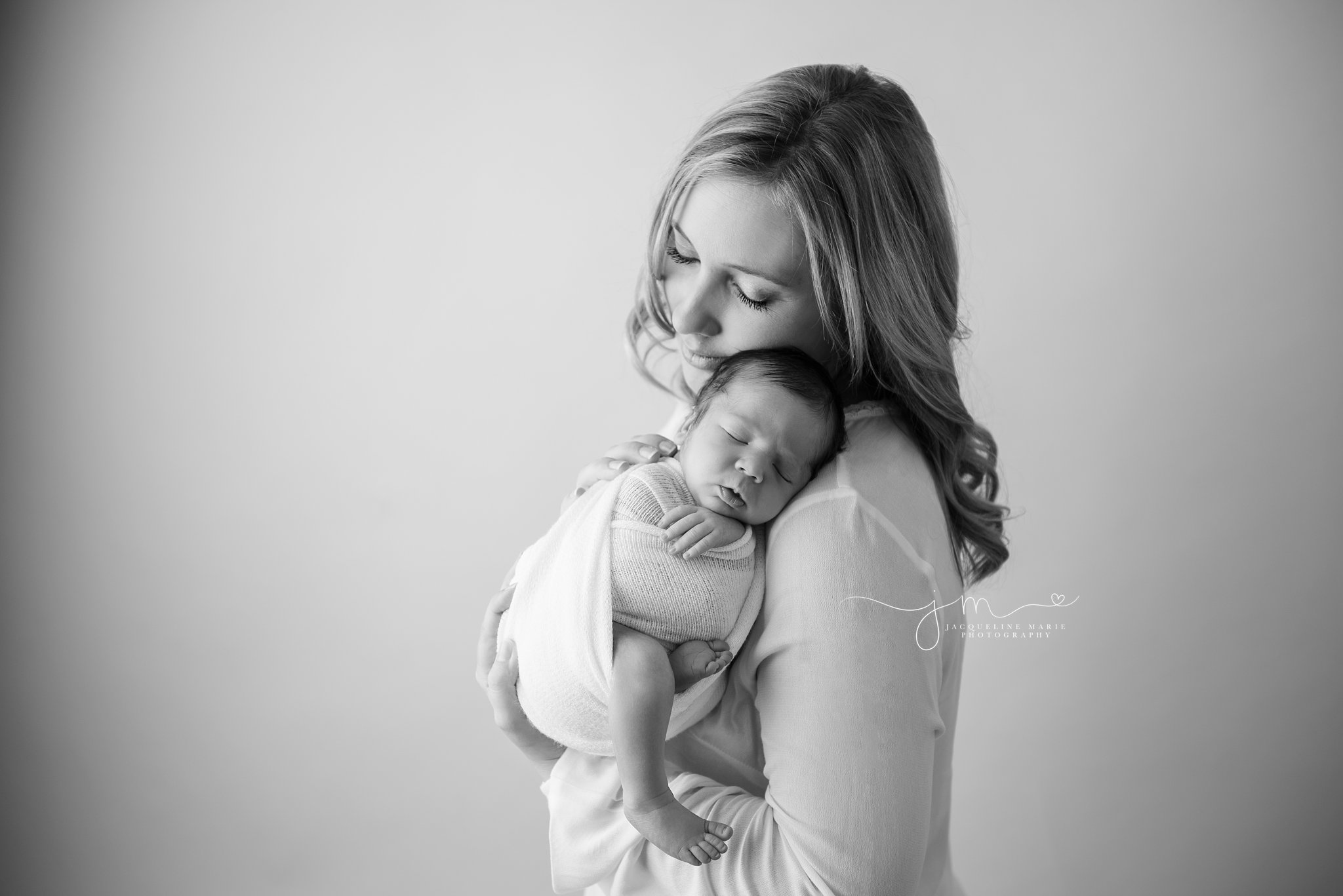 mother holds newborn baby boy and touches his back for newborn pictures in columbus ohio