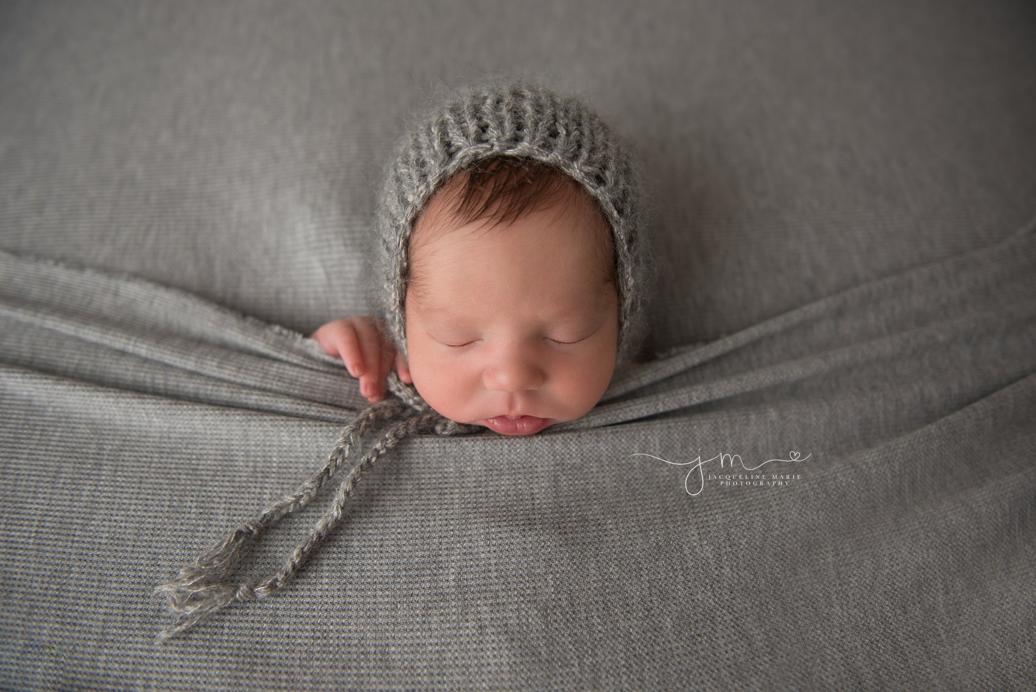 columbus ohio newborn baby boy wears gray bonnet with hands peeking out of gray blanket at jacqueline marie photography studio