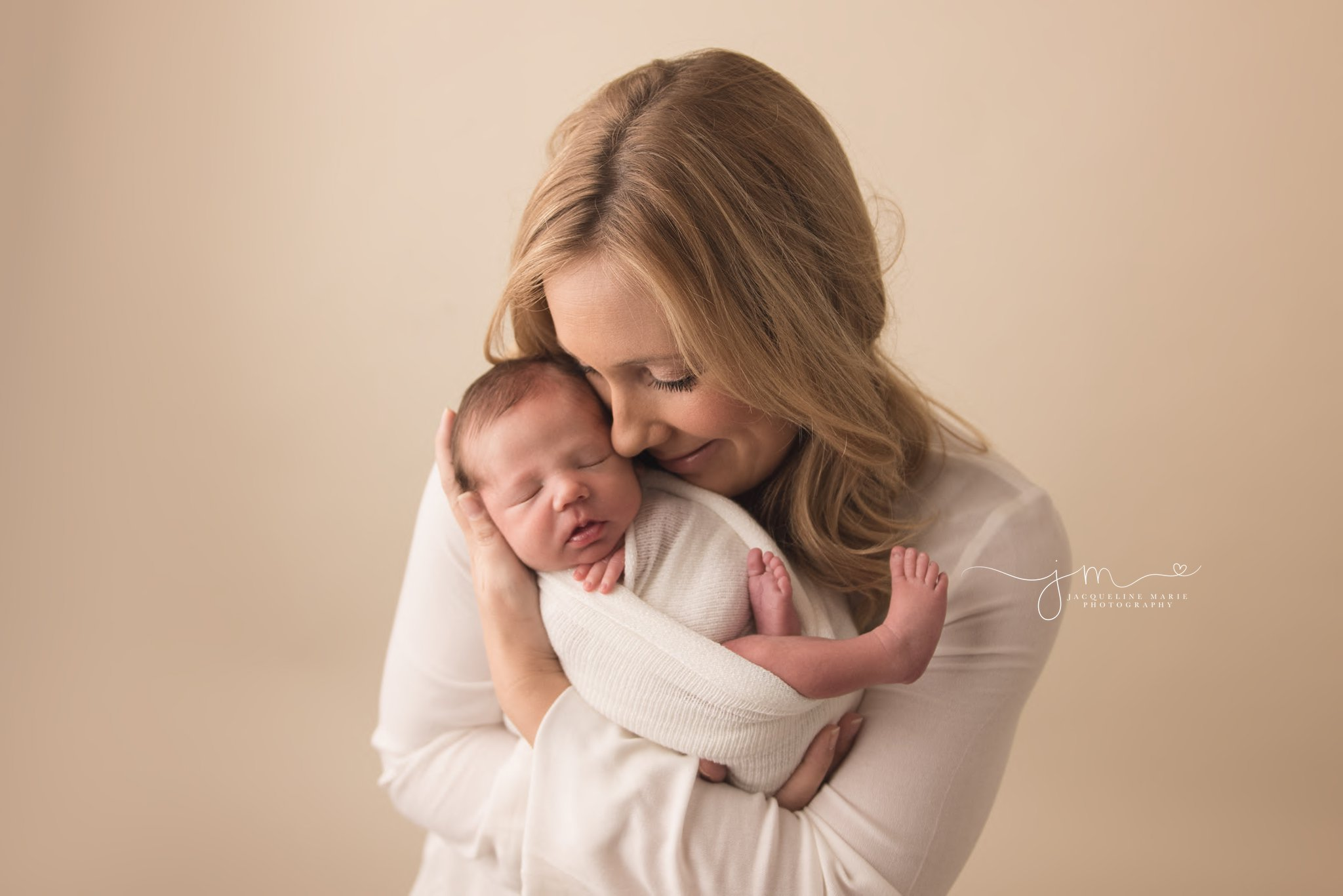 columbus ohio newborn photographer feature image of mother holding son and showing love by smiling at him